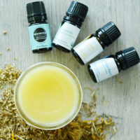 overhead shot of a small half-pint Mason of a yellow-colored arnica and yarrow salve for varicose veins, with four bottles of essential oils (including helichrysum and juniper berry) arranged next to it