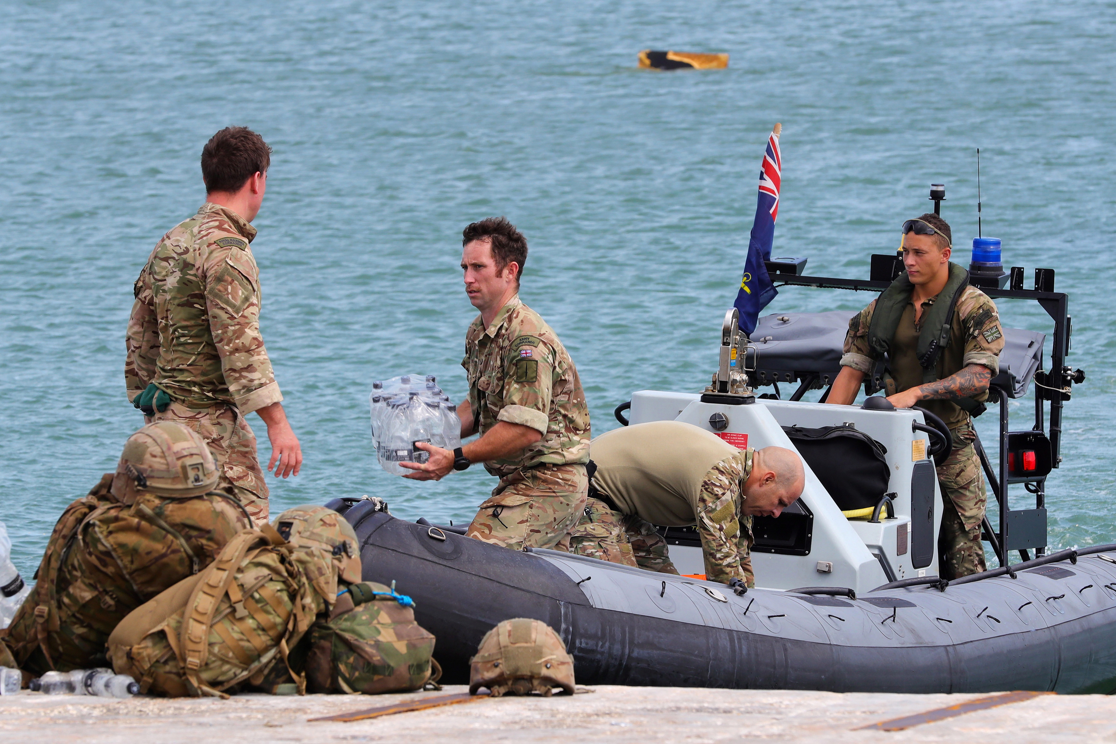 Brit servicemen unload emergency supplies for locals in Great Abaco