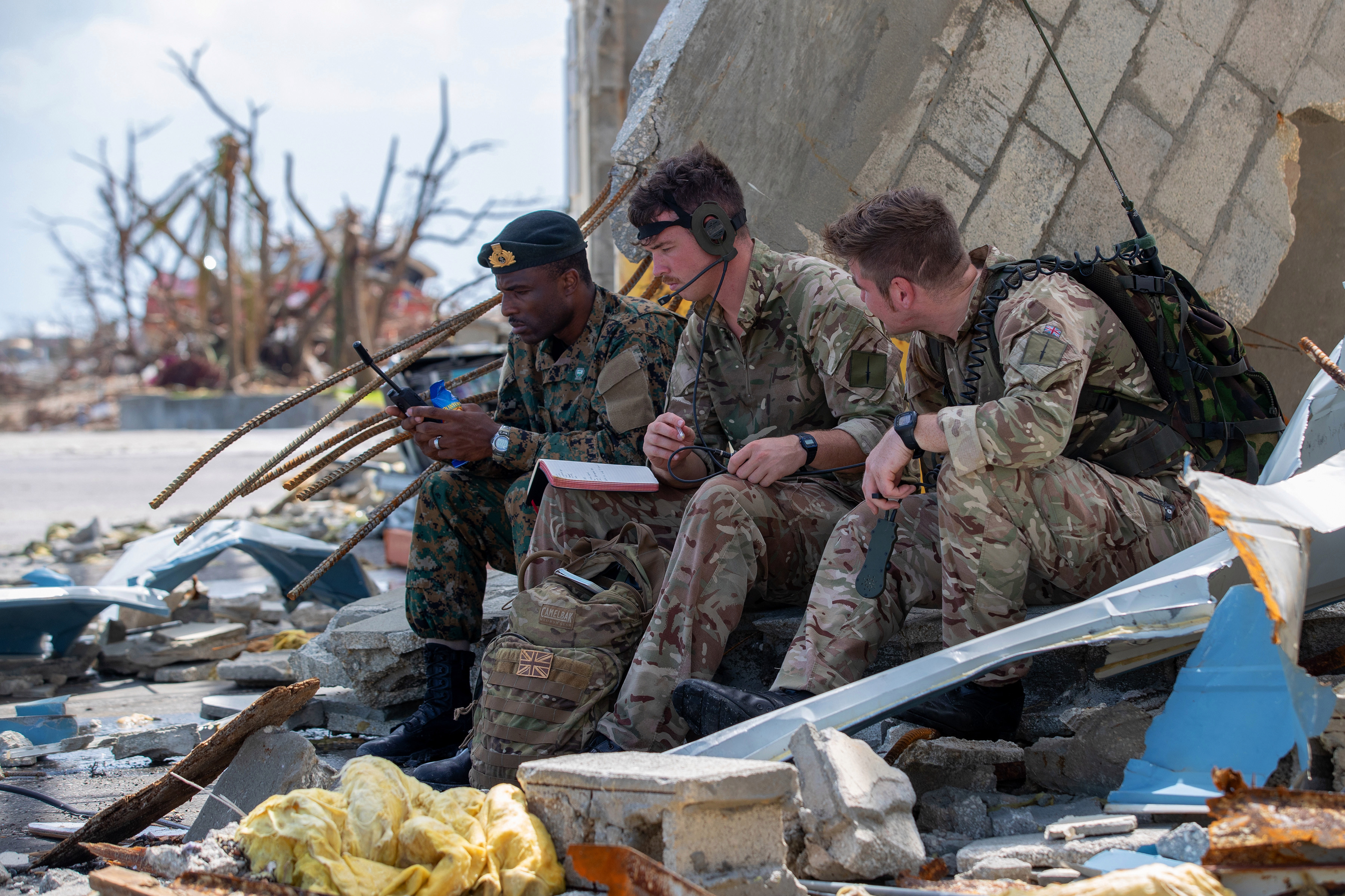 Brit members of the Humanitarian and Disaster Relief team work with a Bahamian soldier