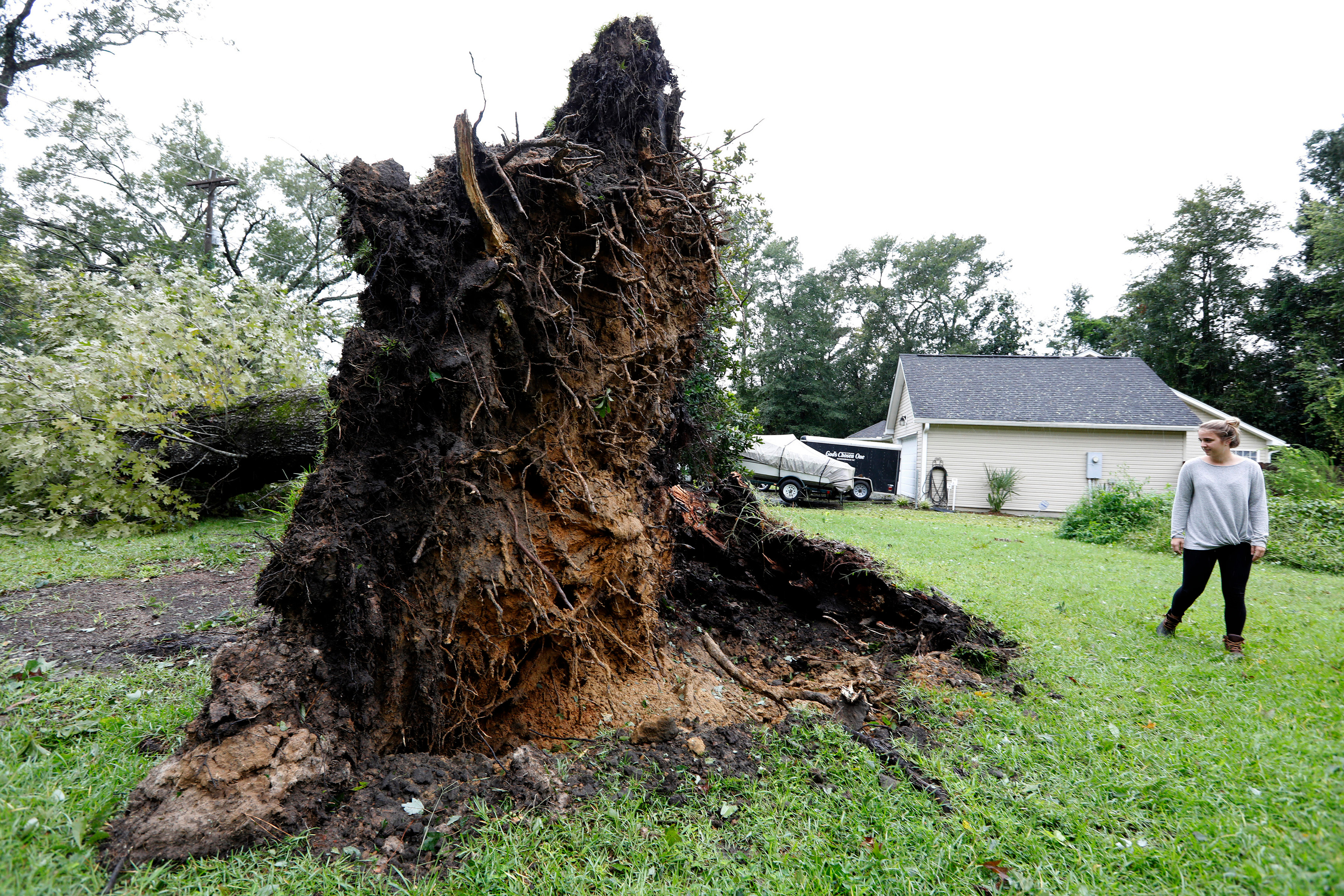 Kelsey Myers looks at an overturned tree in her front yard in Summerville, South Carolina
