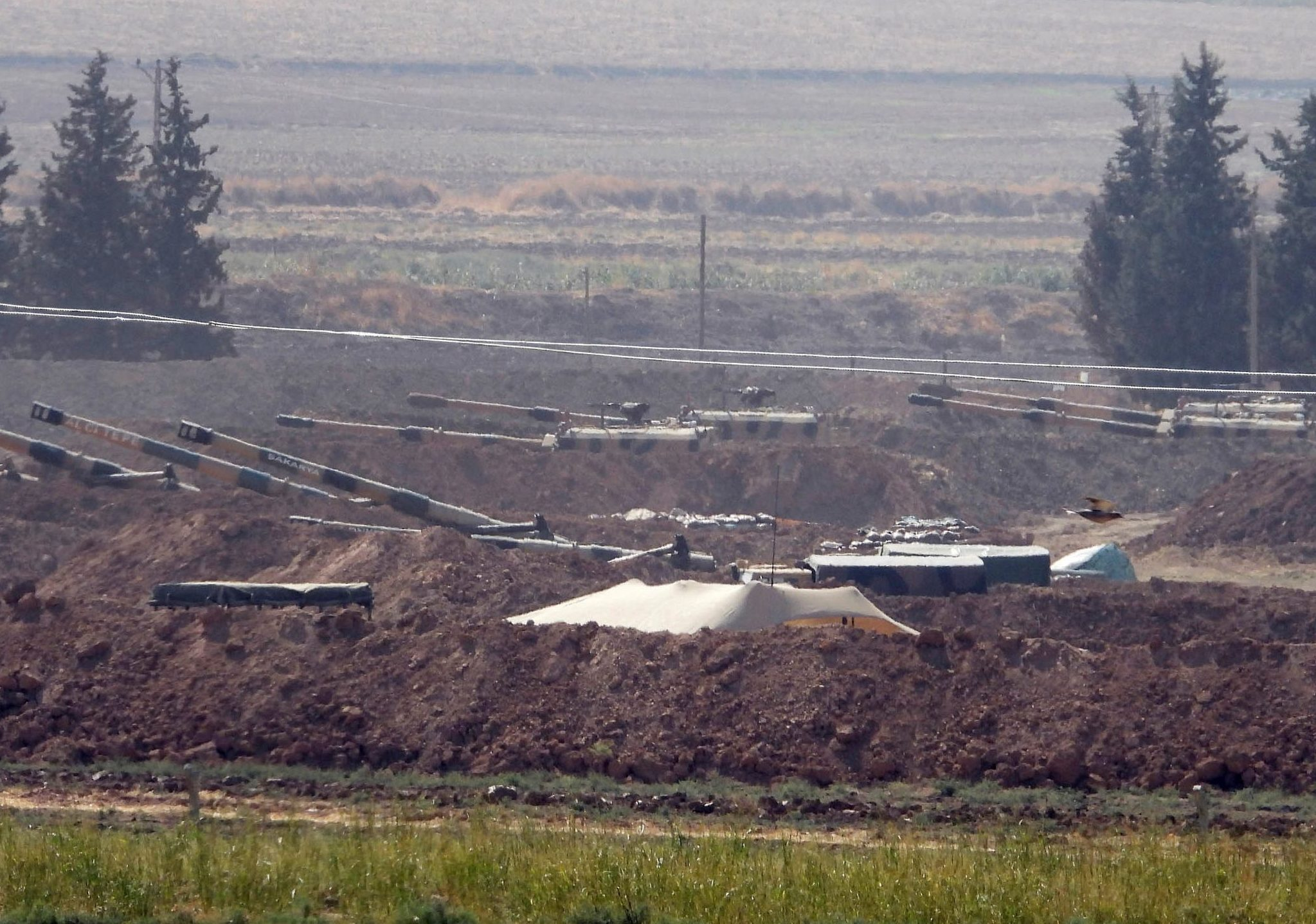 Turkish forces artillery pieces are seen on their new positions near the border with Syria in Sanliurfa province