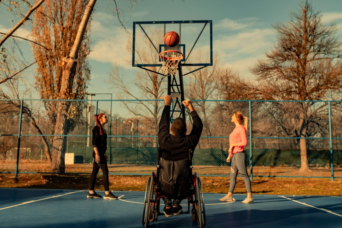 A man in a wheelchair plays basketball with two women.
