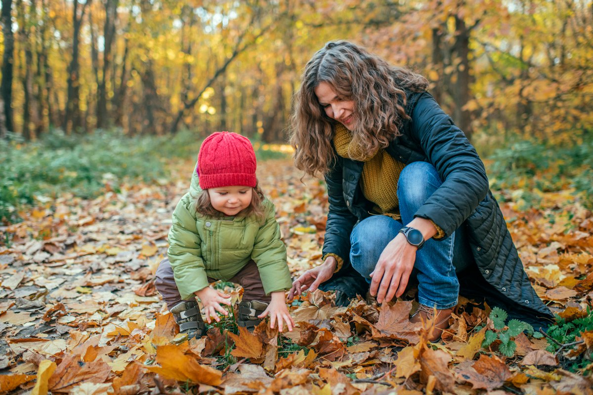 A mother and daughter collect leaves during Autumn.
