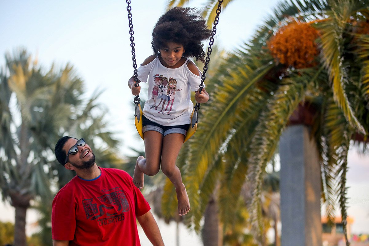 A father pushes his daughter on a swing.
