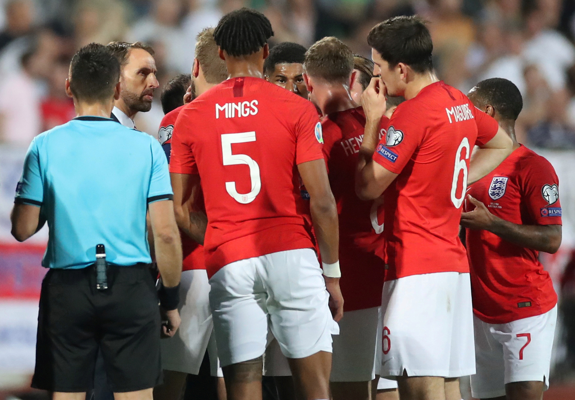 England players and Gareth Southgate talk amongst themselves and to the referee after the sick chanting