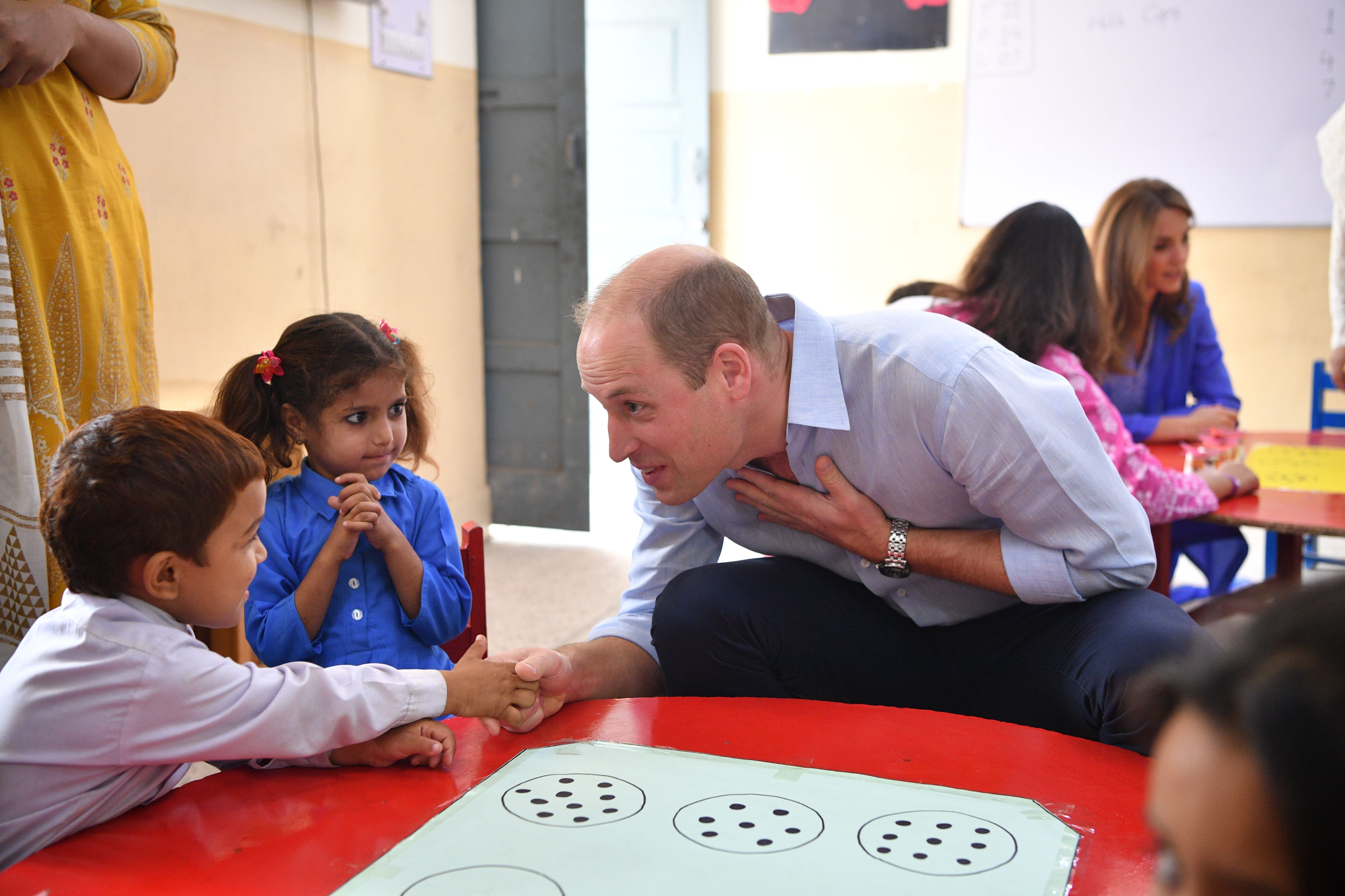 William shook hands with young pupils, but one student didn't look sure