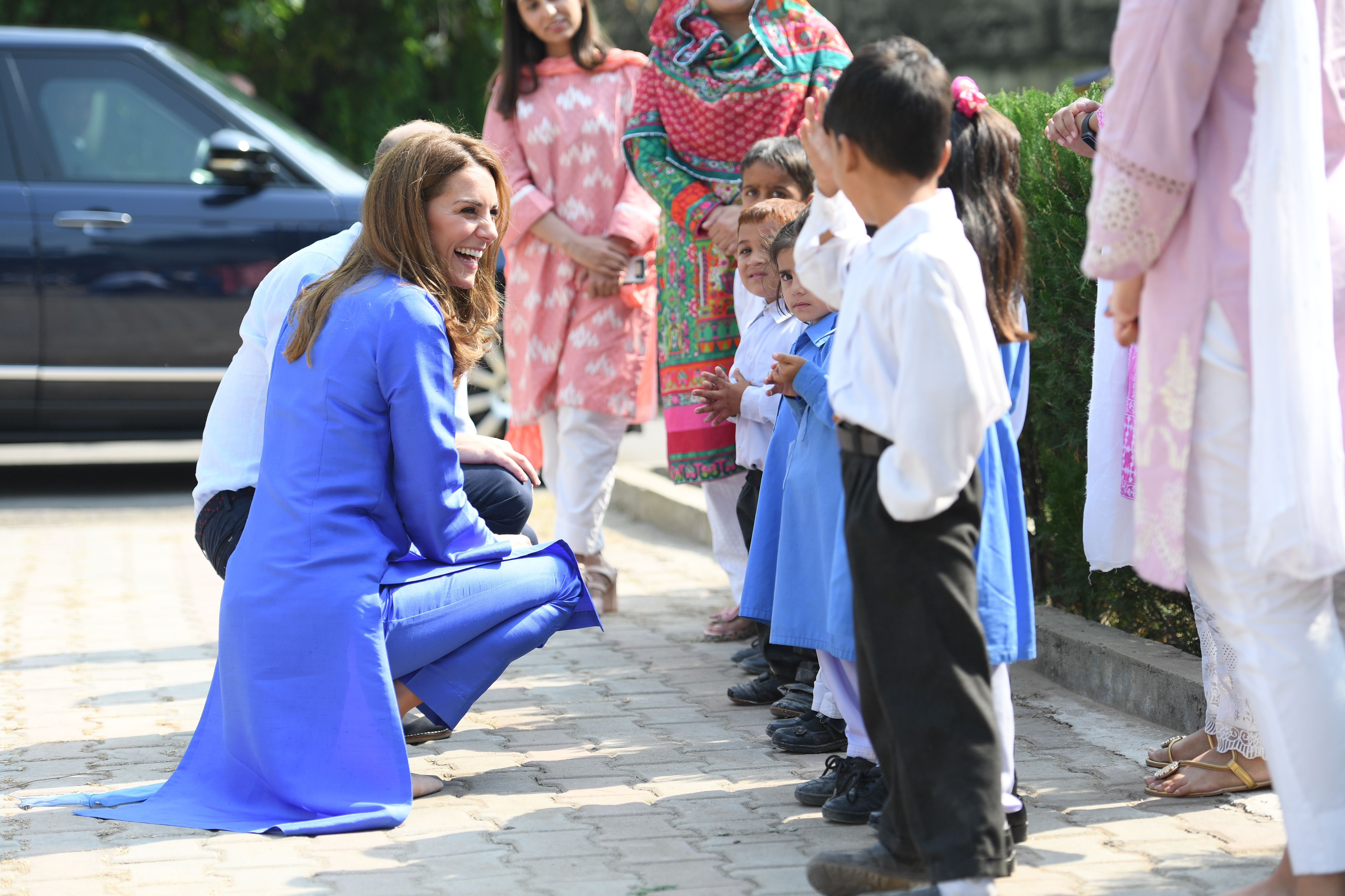 Kate was all smiles as children lined up to greet her