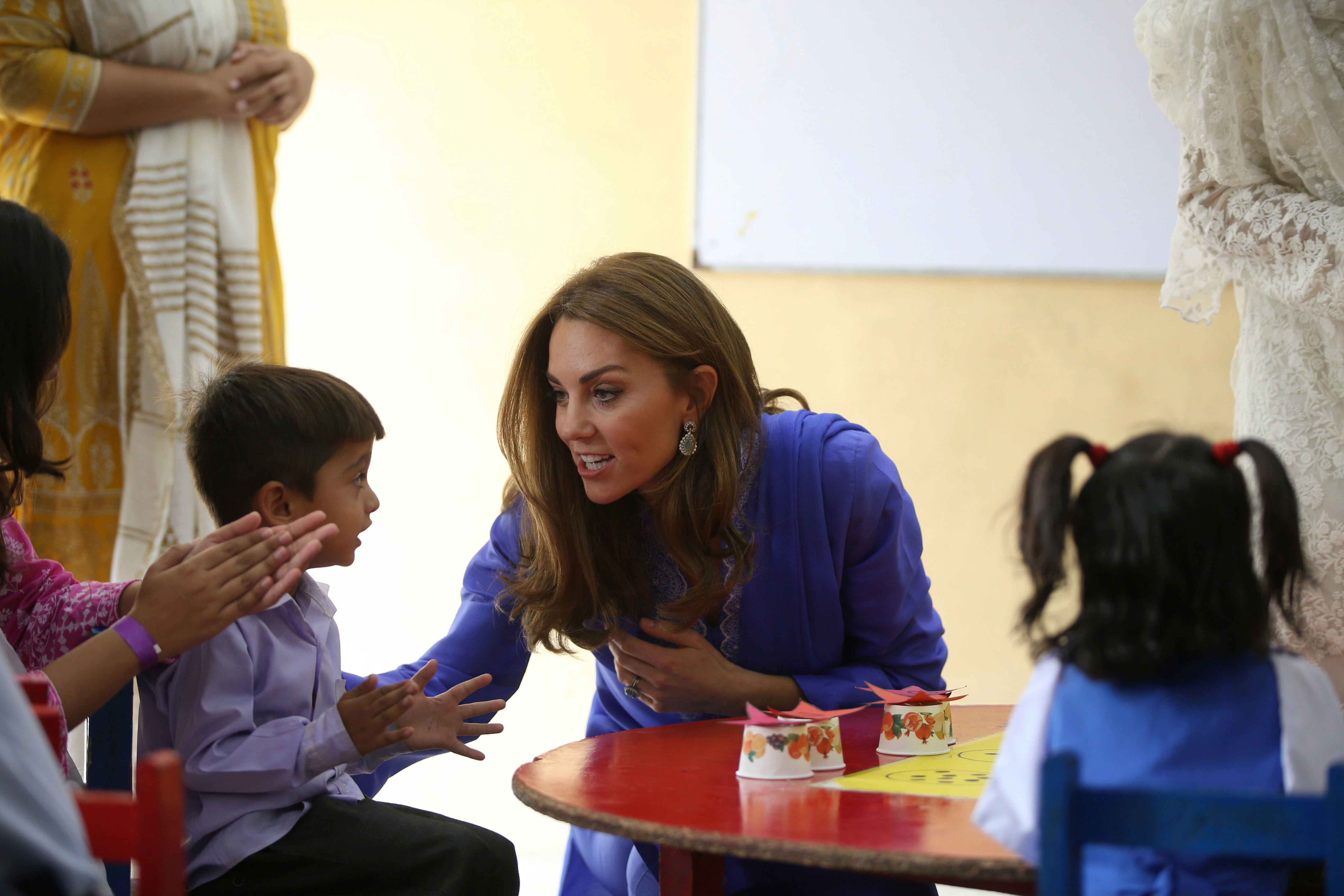 Kate speaks today to one little boy during the visit to Pakistan, which the royals have made without their own three children