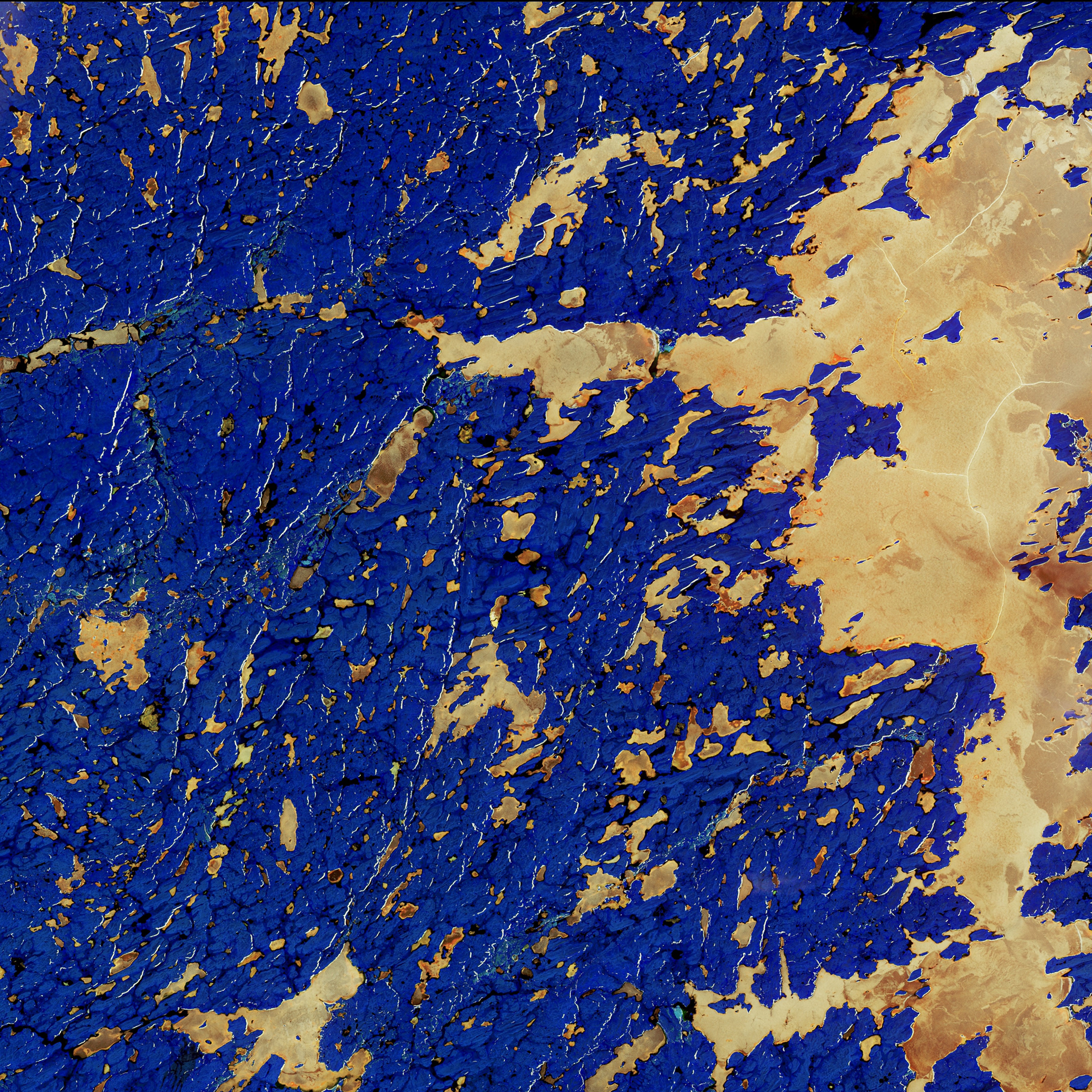 The copper colour in this infrared combination is the presence of lake ice in the Northwest Territories in northern Canada. The lake on the right side is Whitefish Lake, in a region with numerous glacial landforms. Bright wrinkle-like lines are eskers, ridges made of sand and gravel formed by glacial sediments deposited by meltwater rivers flowing on the ice. The blue colour is land dominated by shrub tundra with some spruce stands.