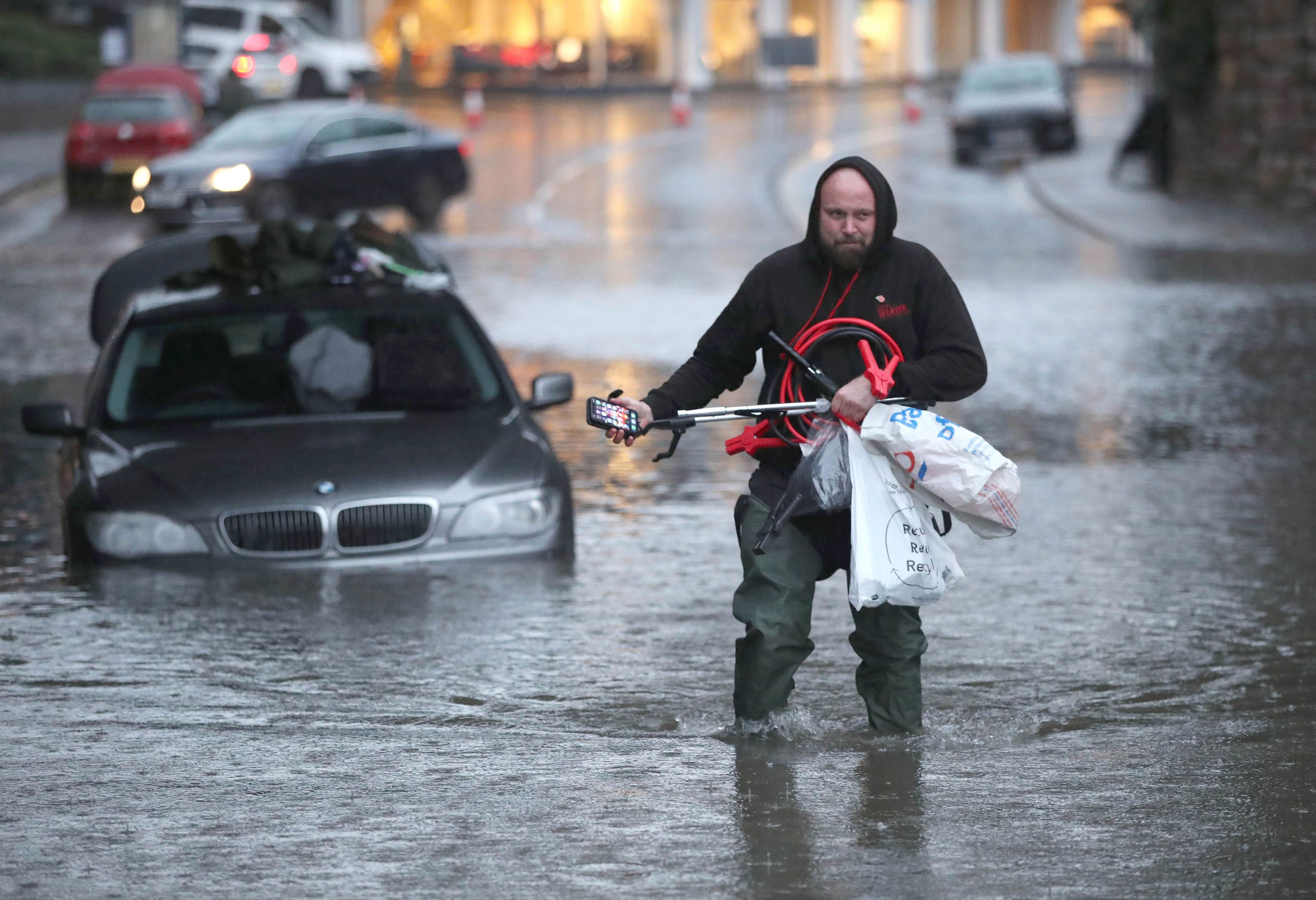 UK flooding: A man wades through a flooded street in Sheffield this afternoon