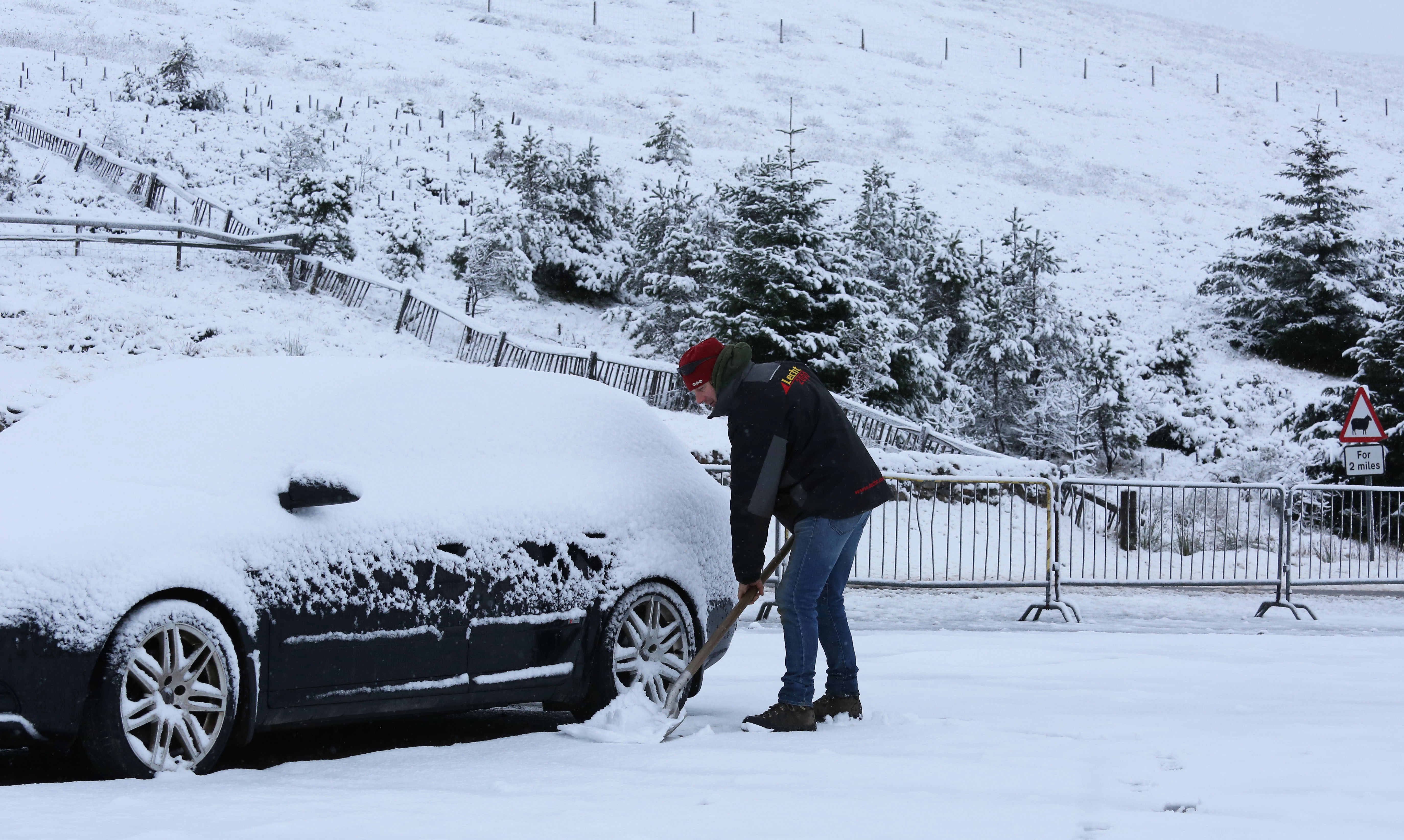 Commuter Neil Robb had to clear snow from around his car first thing this morning in the Scottish village of Tomintoul