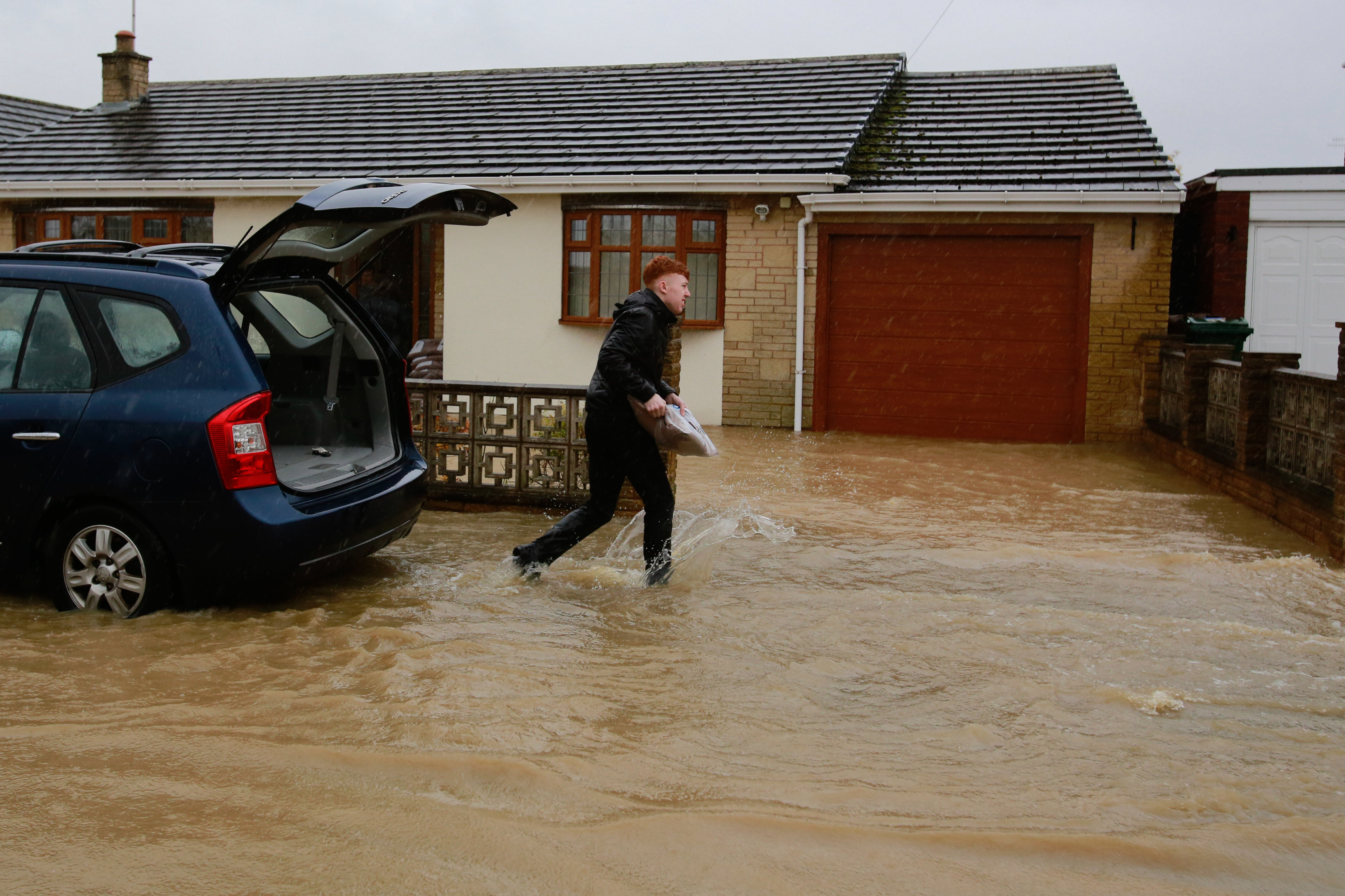 A resident tries to save his home in Whiston from being flooded with sandbags