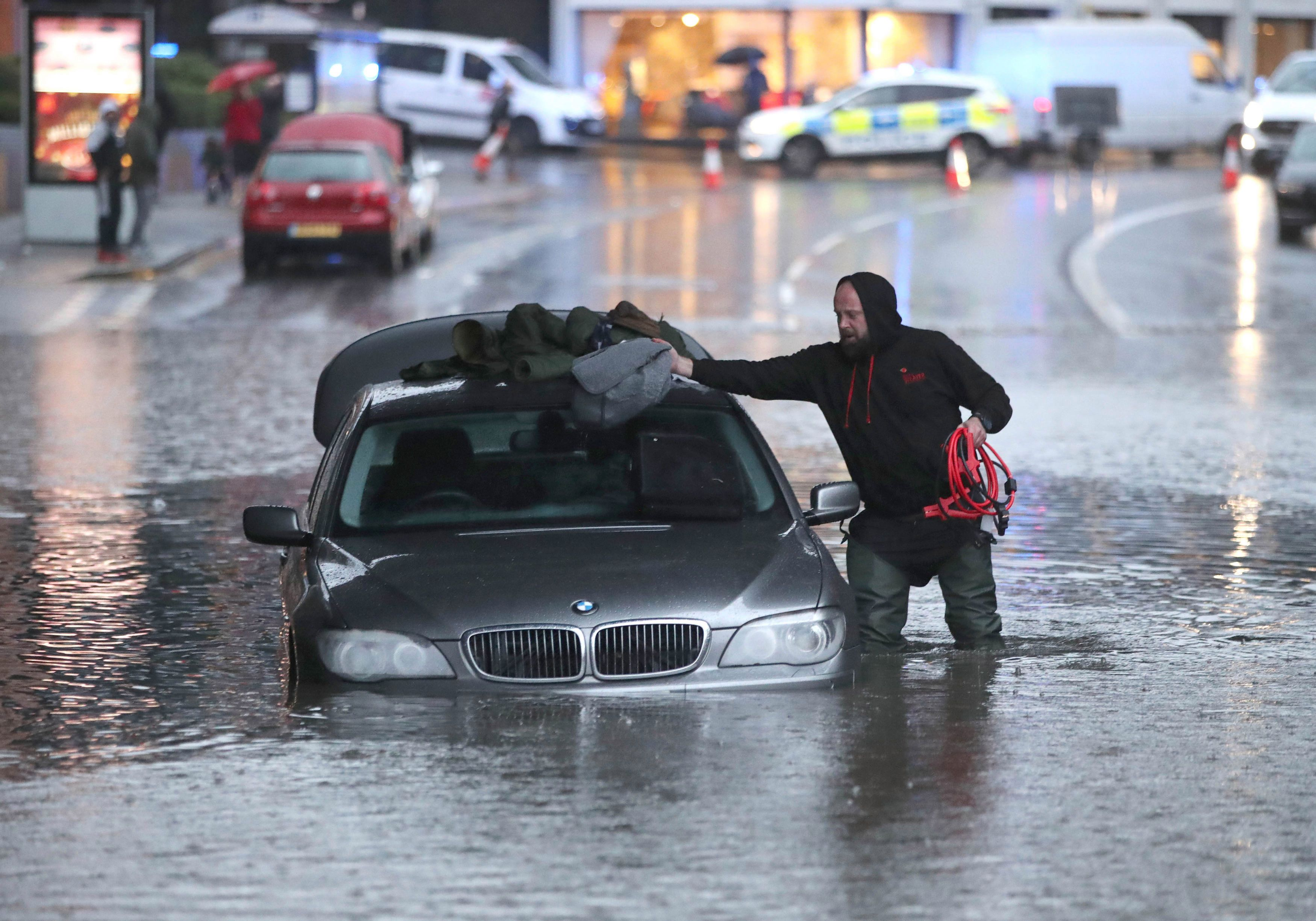 A man abandons his car in a flooded street in Sheffield