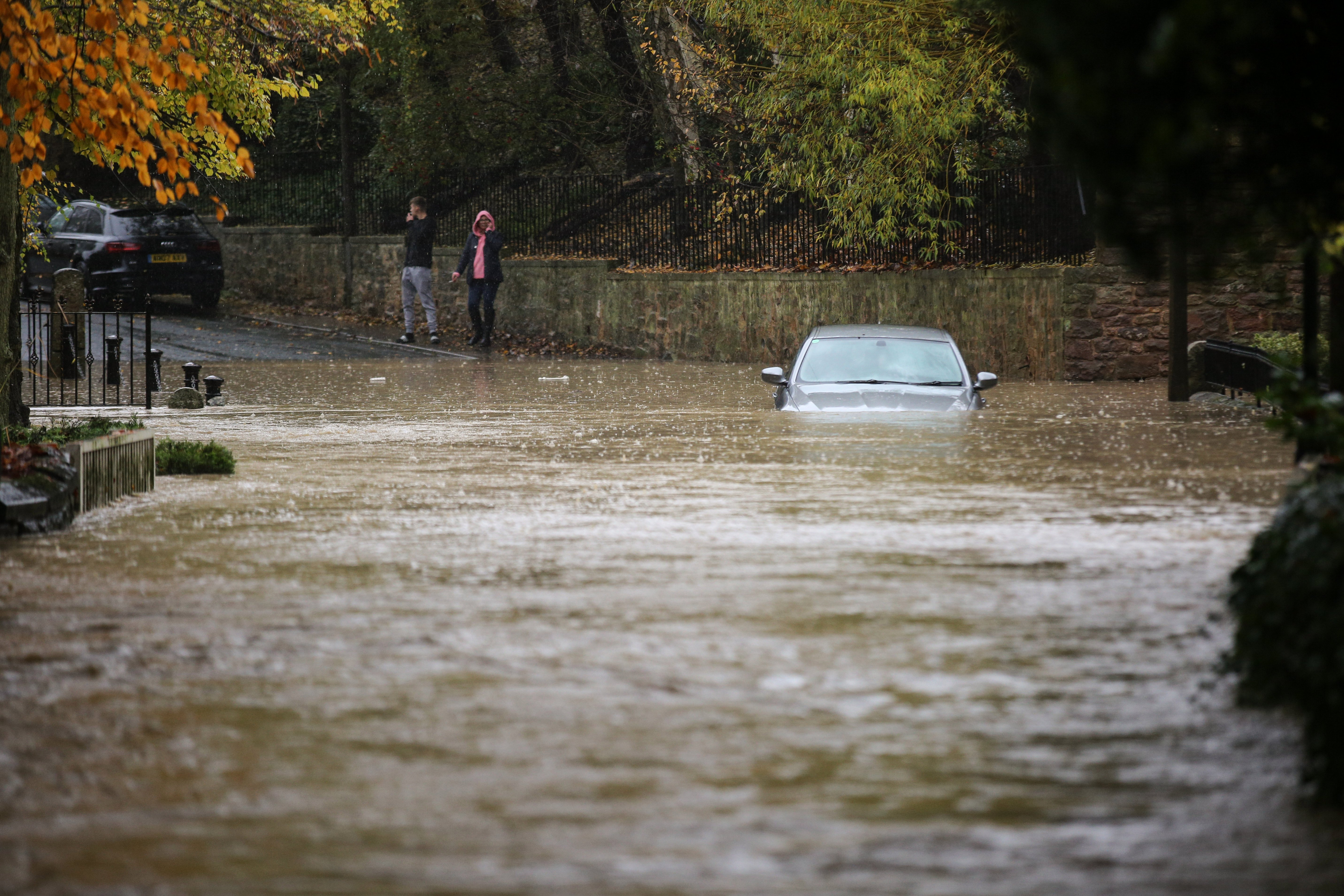 A car is stuck in the flooding in the village of Whiston near Sheffield