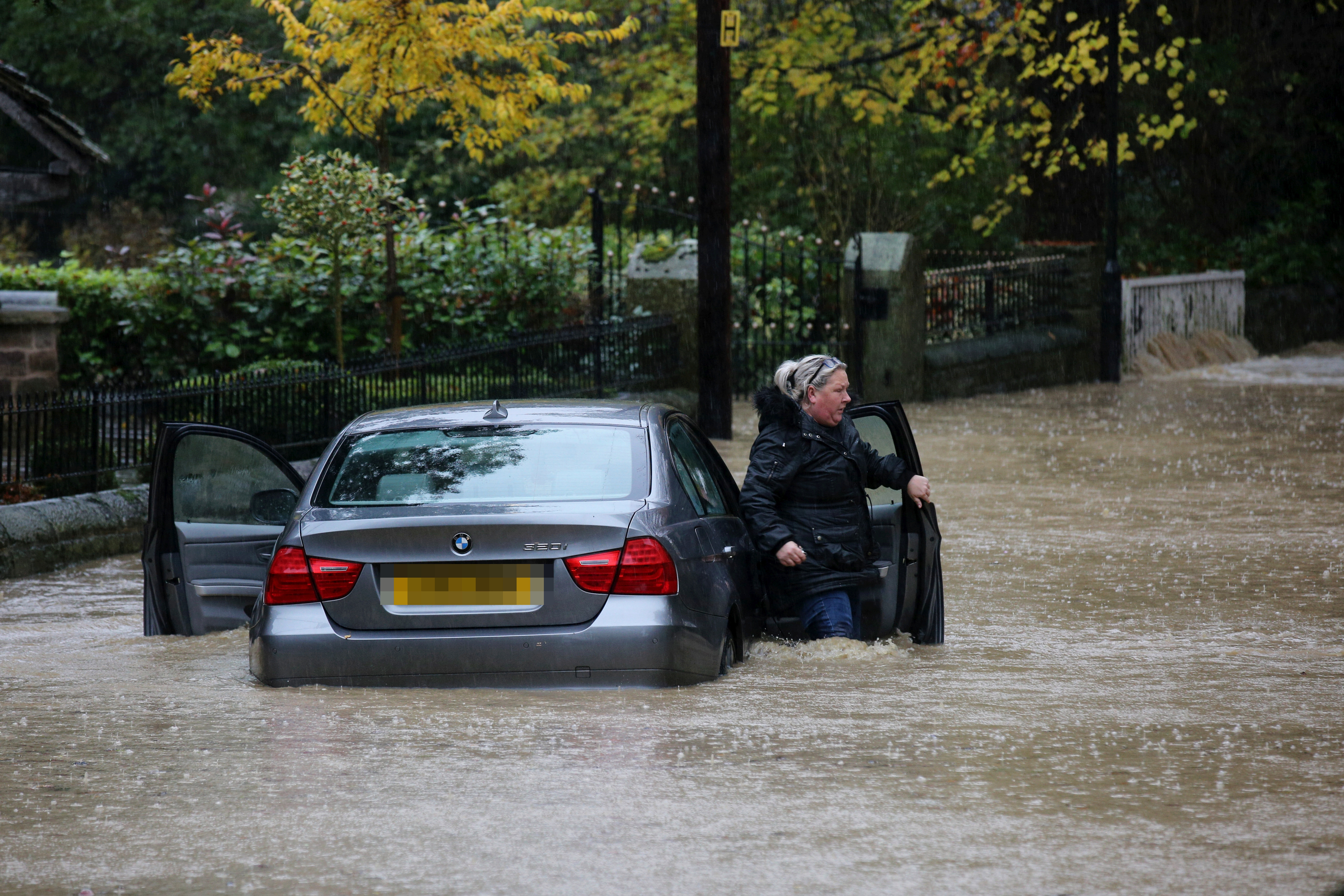 A BMW driver gets stuck trying to drive through deep flood water as it rises in the village of Whiston near Sheffield