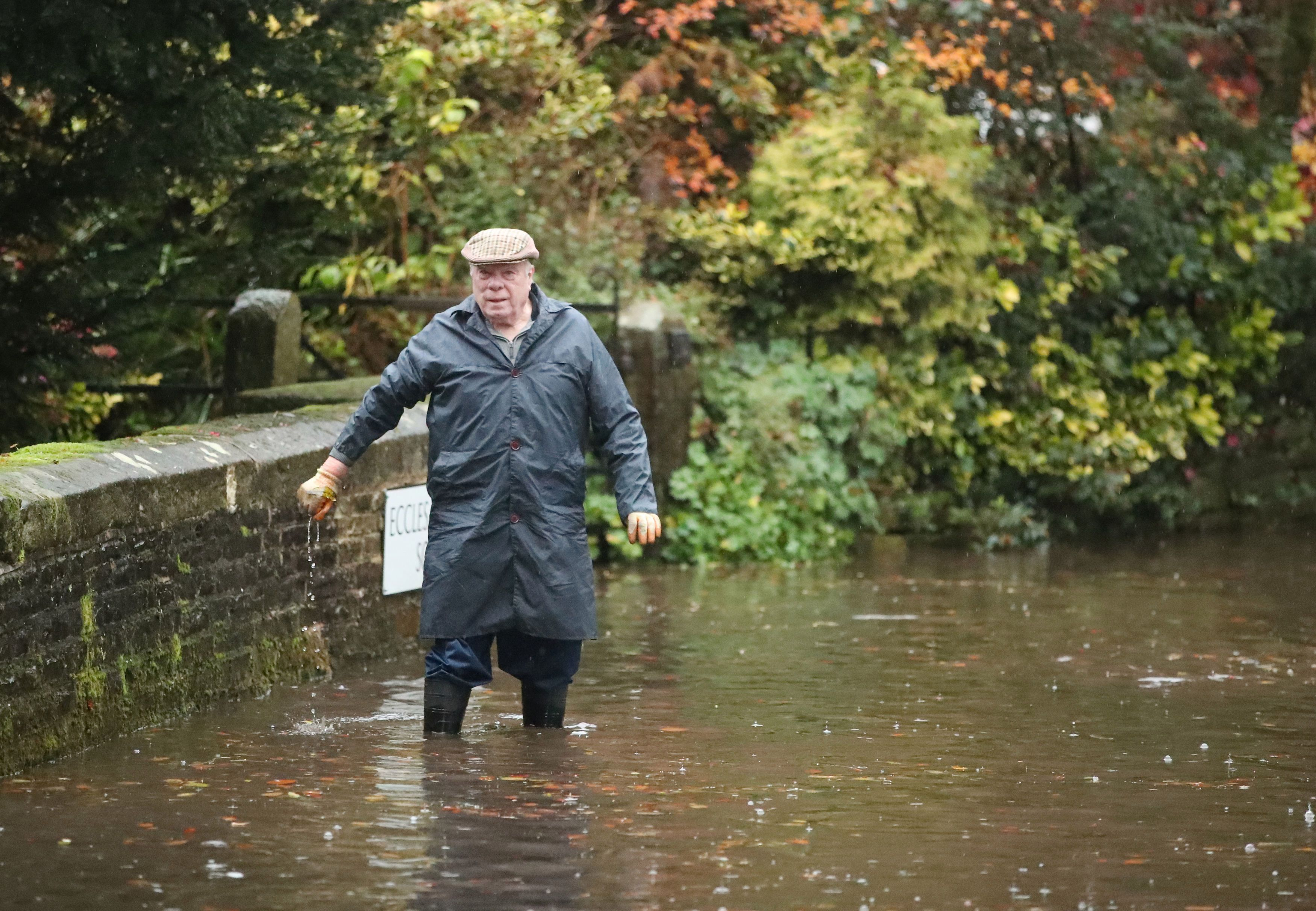 A man wades through the floods in the village of Whirlow near Sheffield