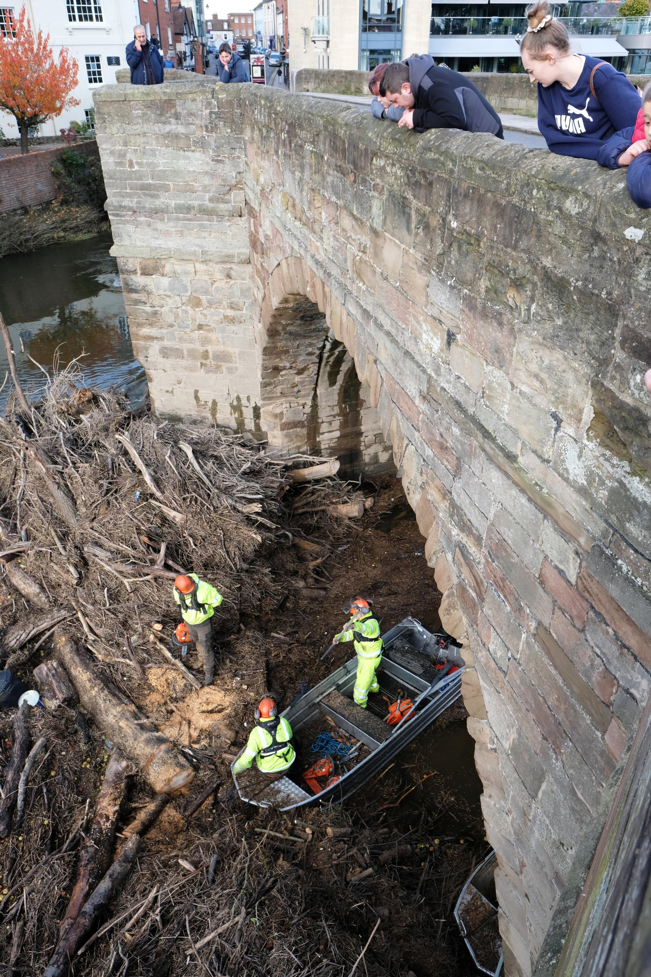 Environment Agency staff work to clear the debris blocking the central arches on the Wye Bridge in Hereford