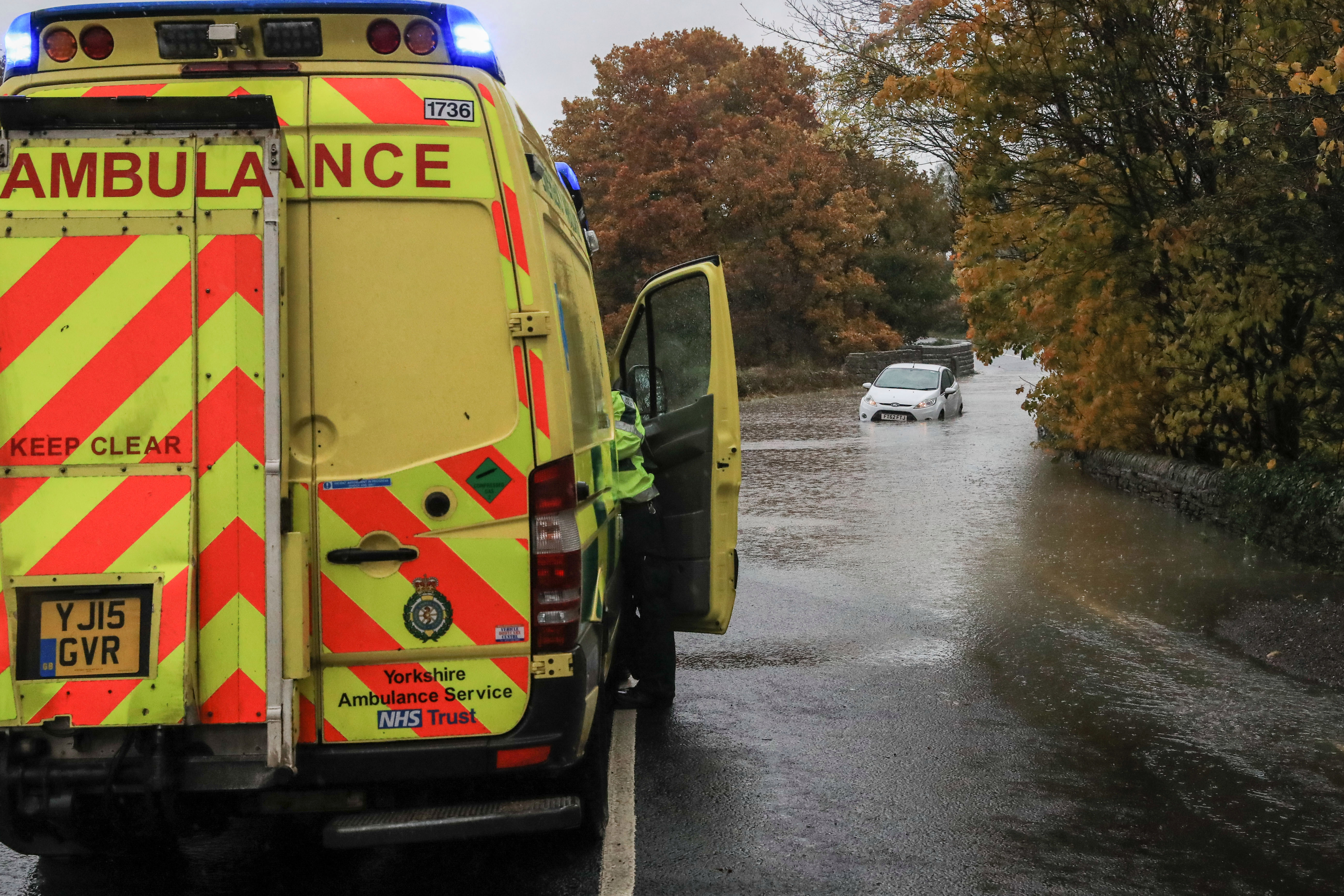 An ambulance stops to help rescue occupants of a white Ford Fiesta as it gets stranded in flood water in Penistone, Barnsley