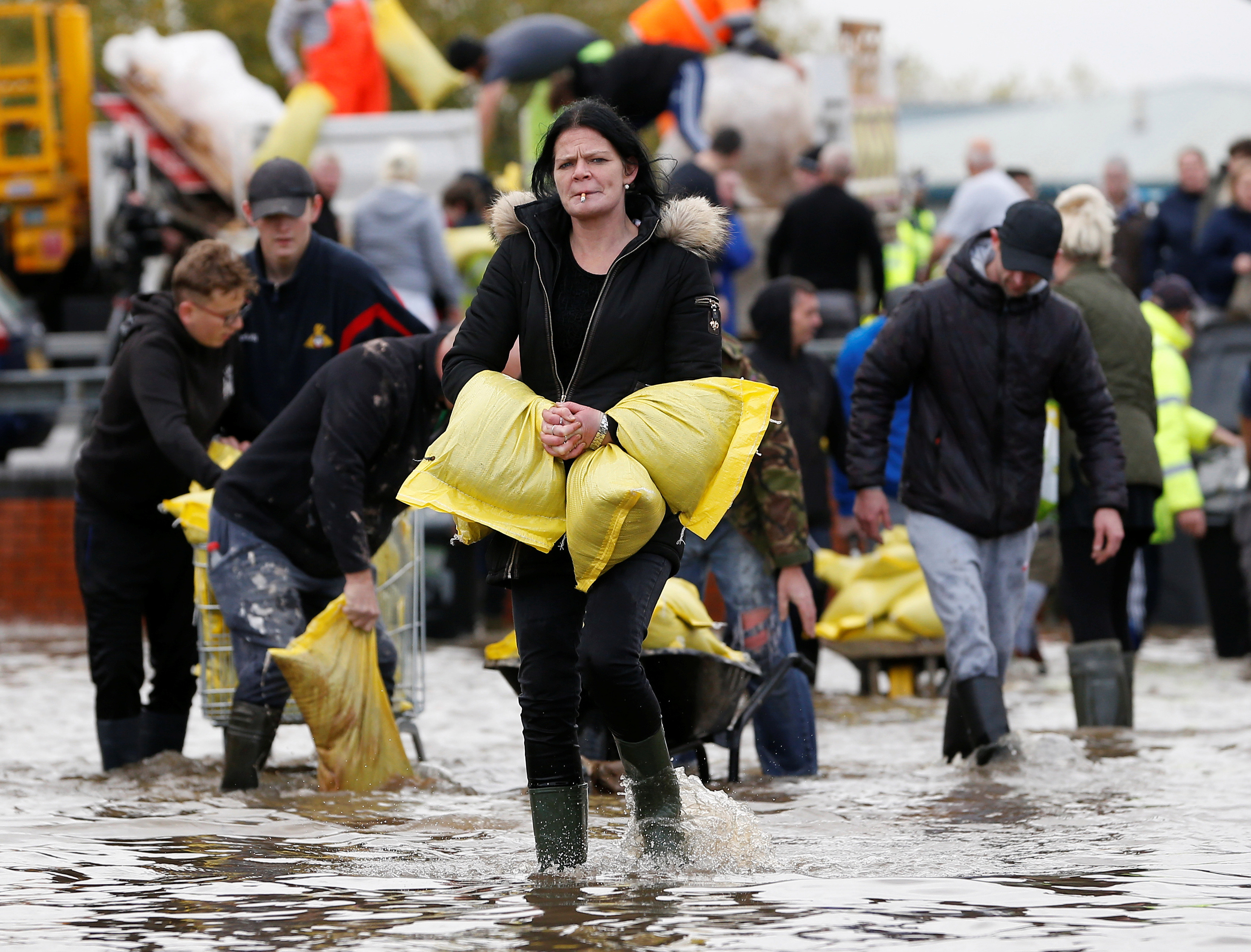 Residents carry sandbags in a flooded area of Bentley, north of Doncaster