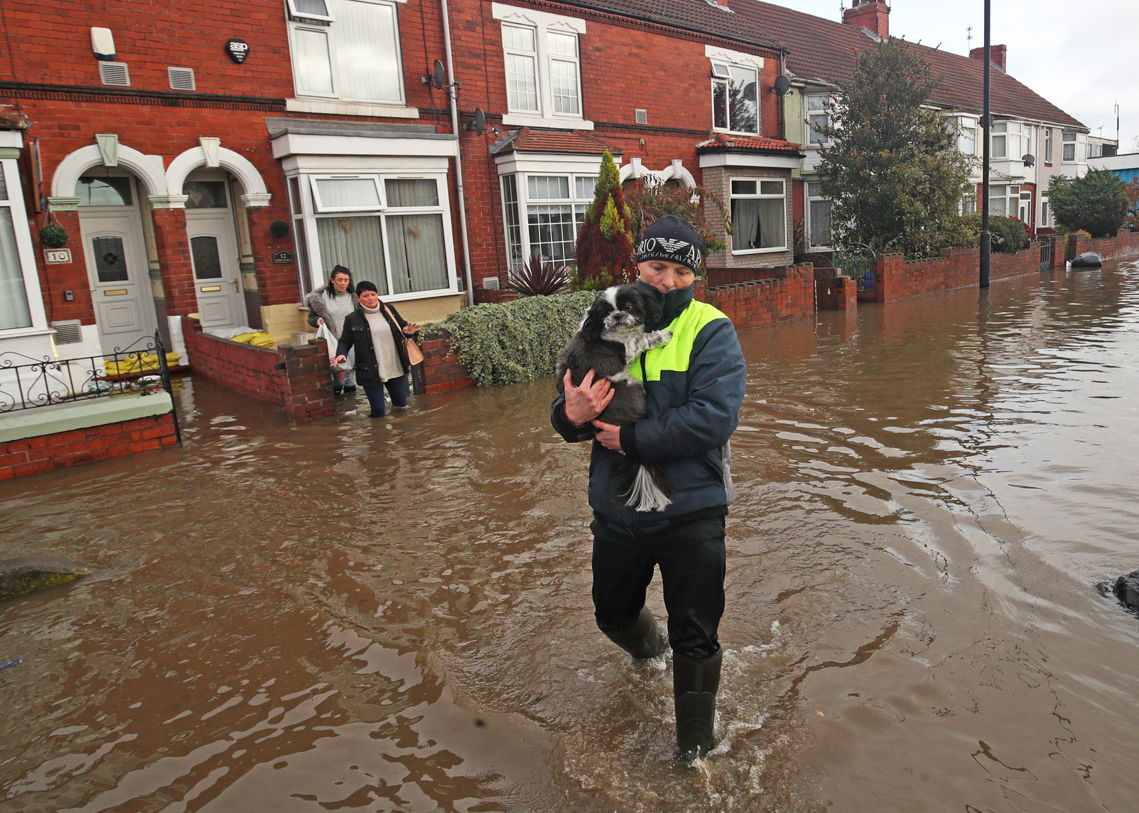 A dog is carried to safety after residents evacuate their homes in Doncaster