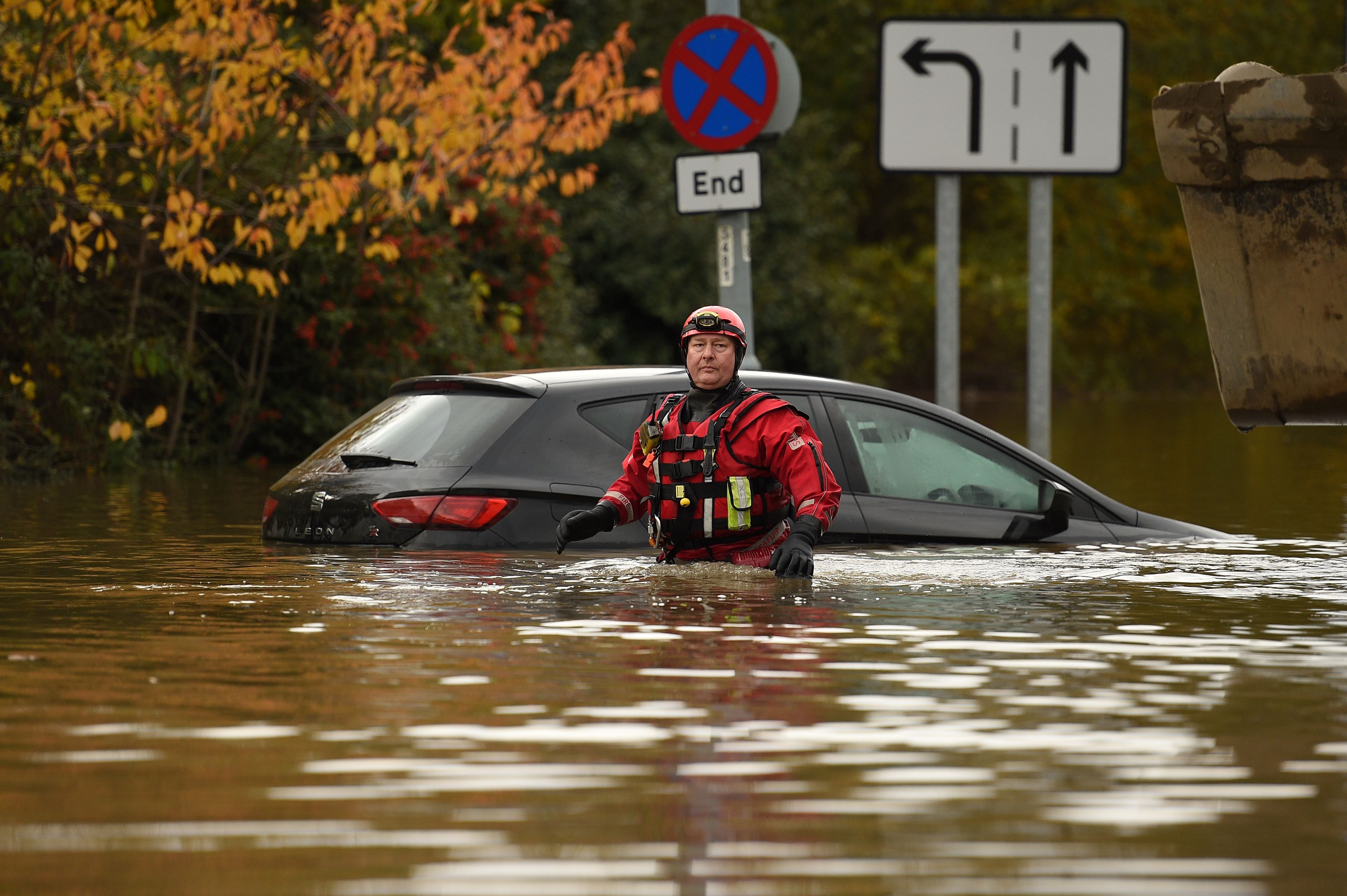 A firefighter battles his way through flood water near an abandoned car in Rotherham