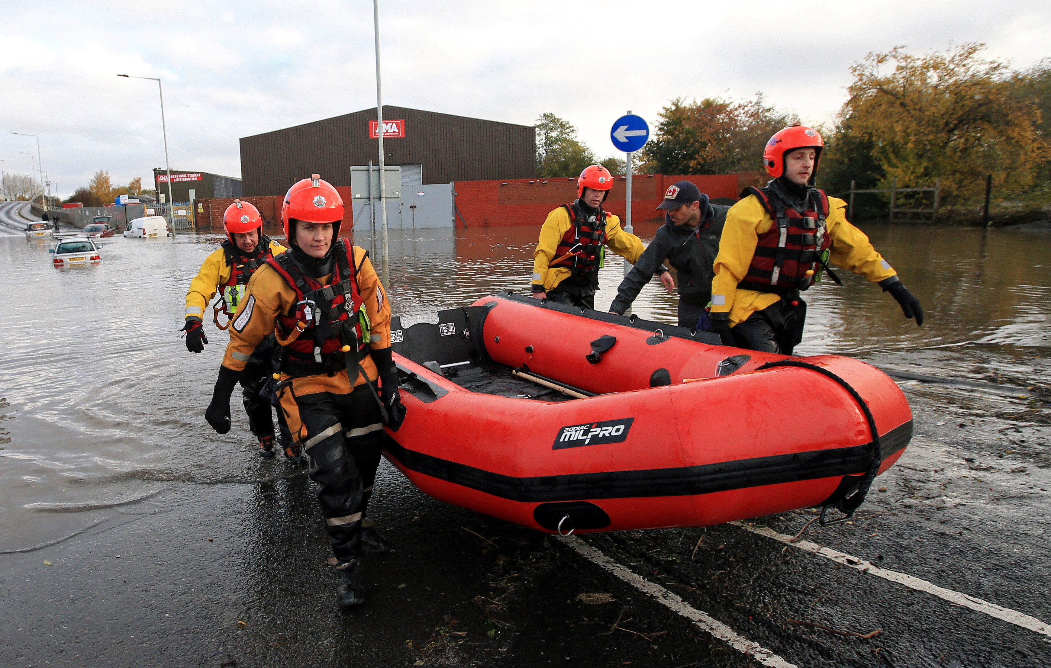 Rescuers carry an inflatable raft after flooding in Rotherham, Sheffield