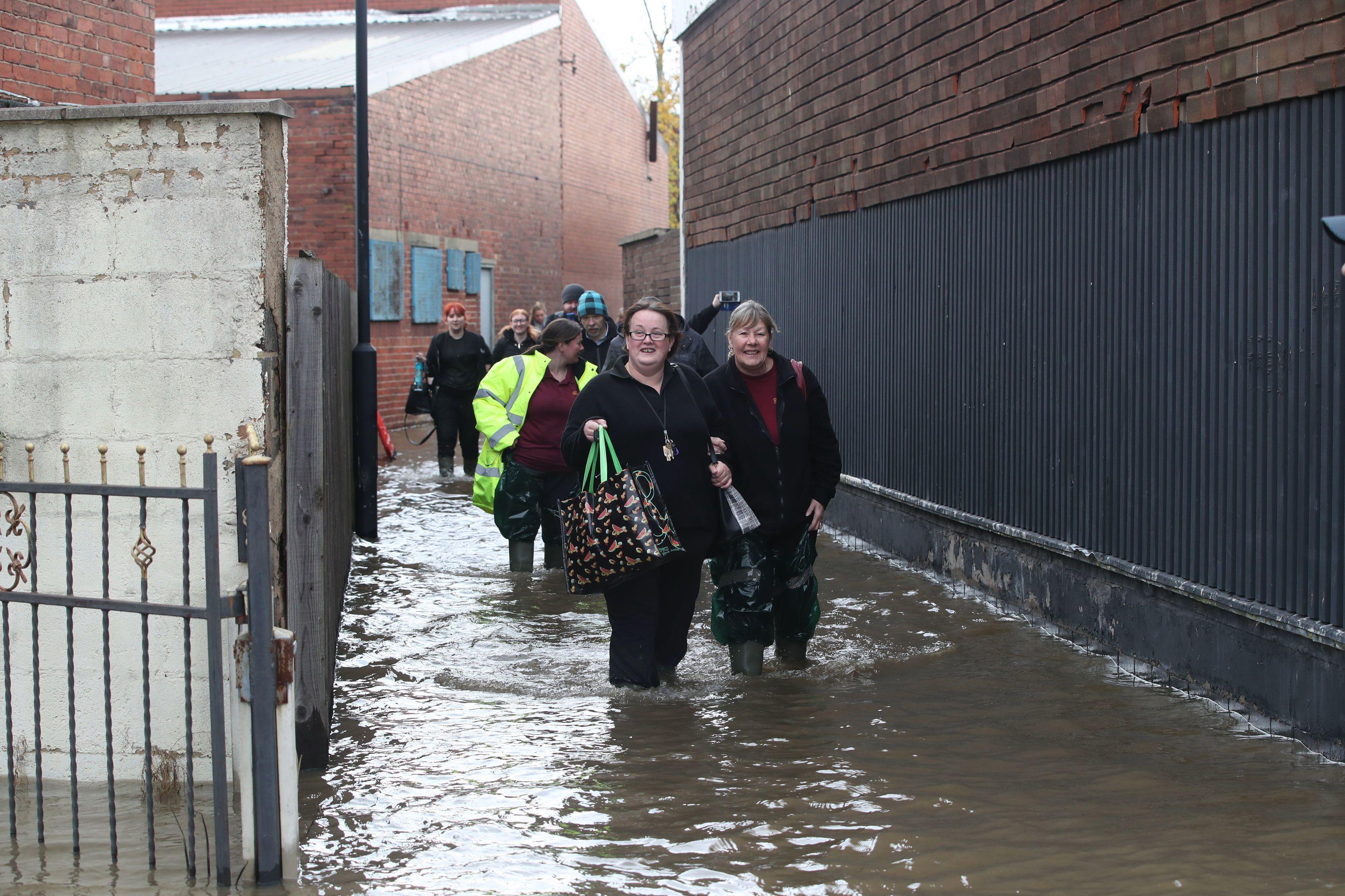 Workers walk through flood water as they in Doncaster