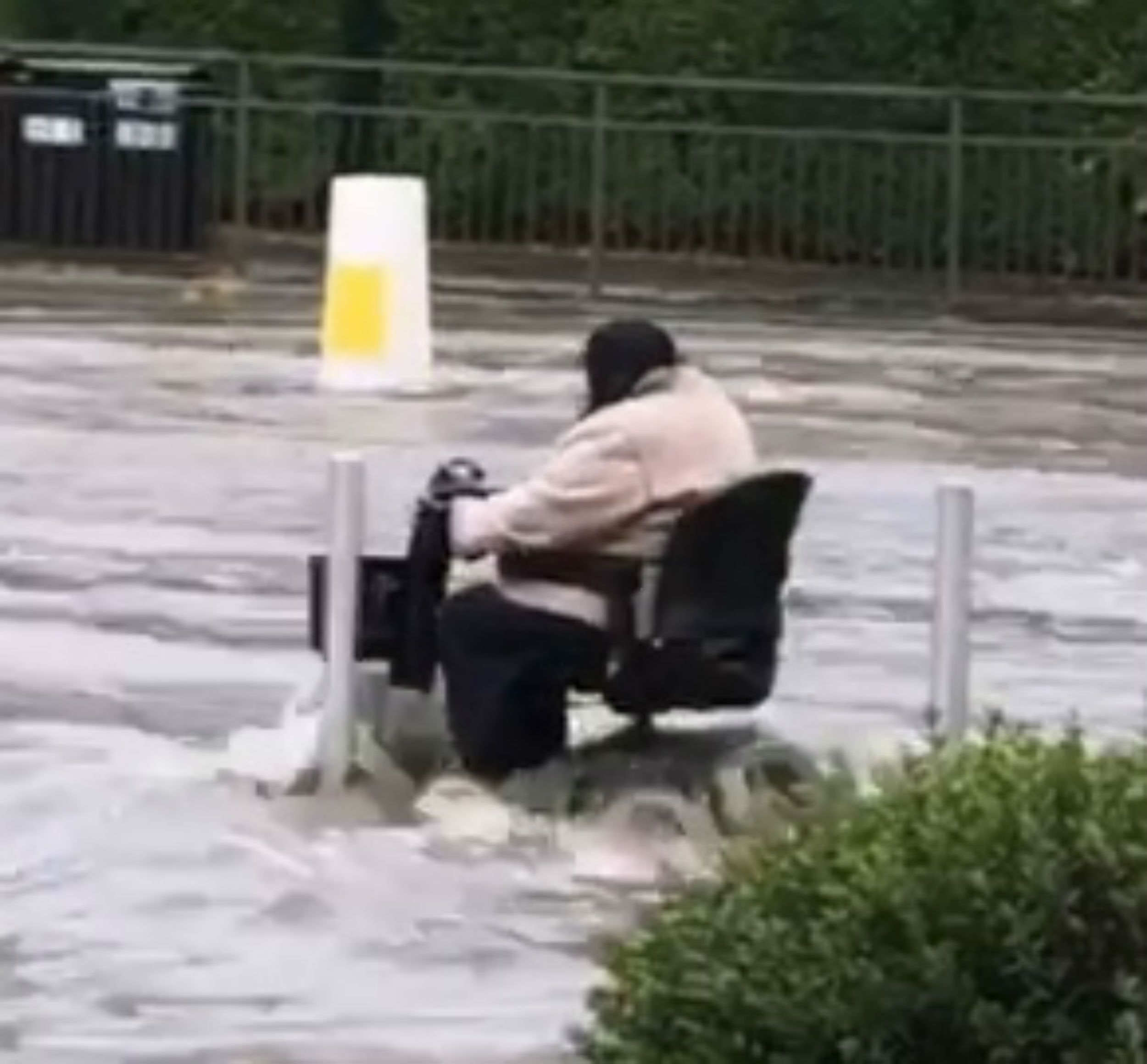 An elderly lady powers her way through the flood water on her mobility scooter in Sheffield