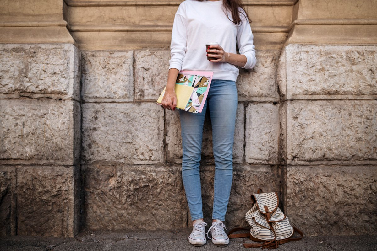 A woman holding a folder, coffee and book bag leans against a wall.