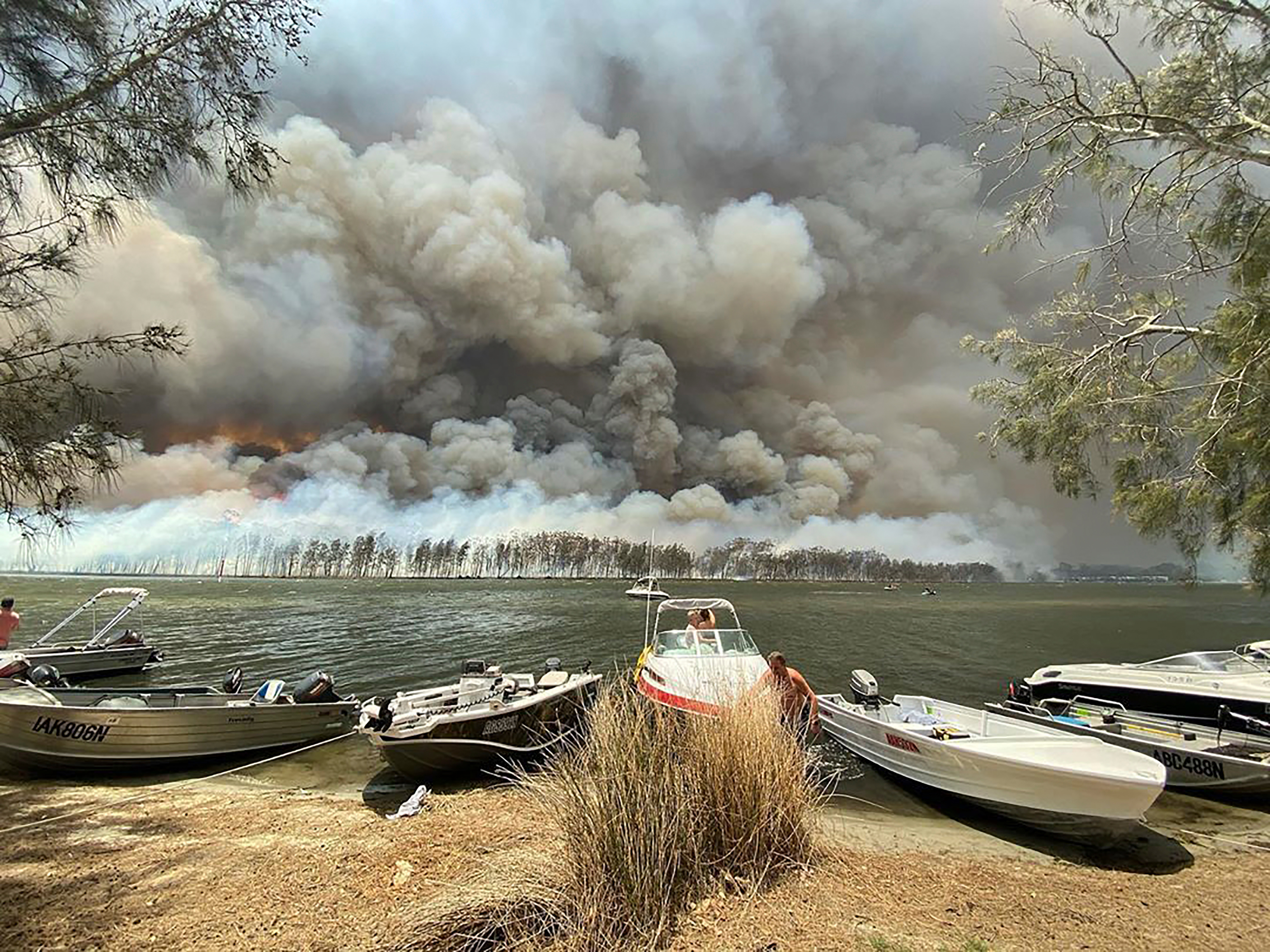 Boats are pulled ashore as smoke and wildfires rage behind Lake Conjola on the South Coast of New South Wales