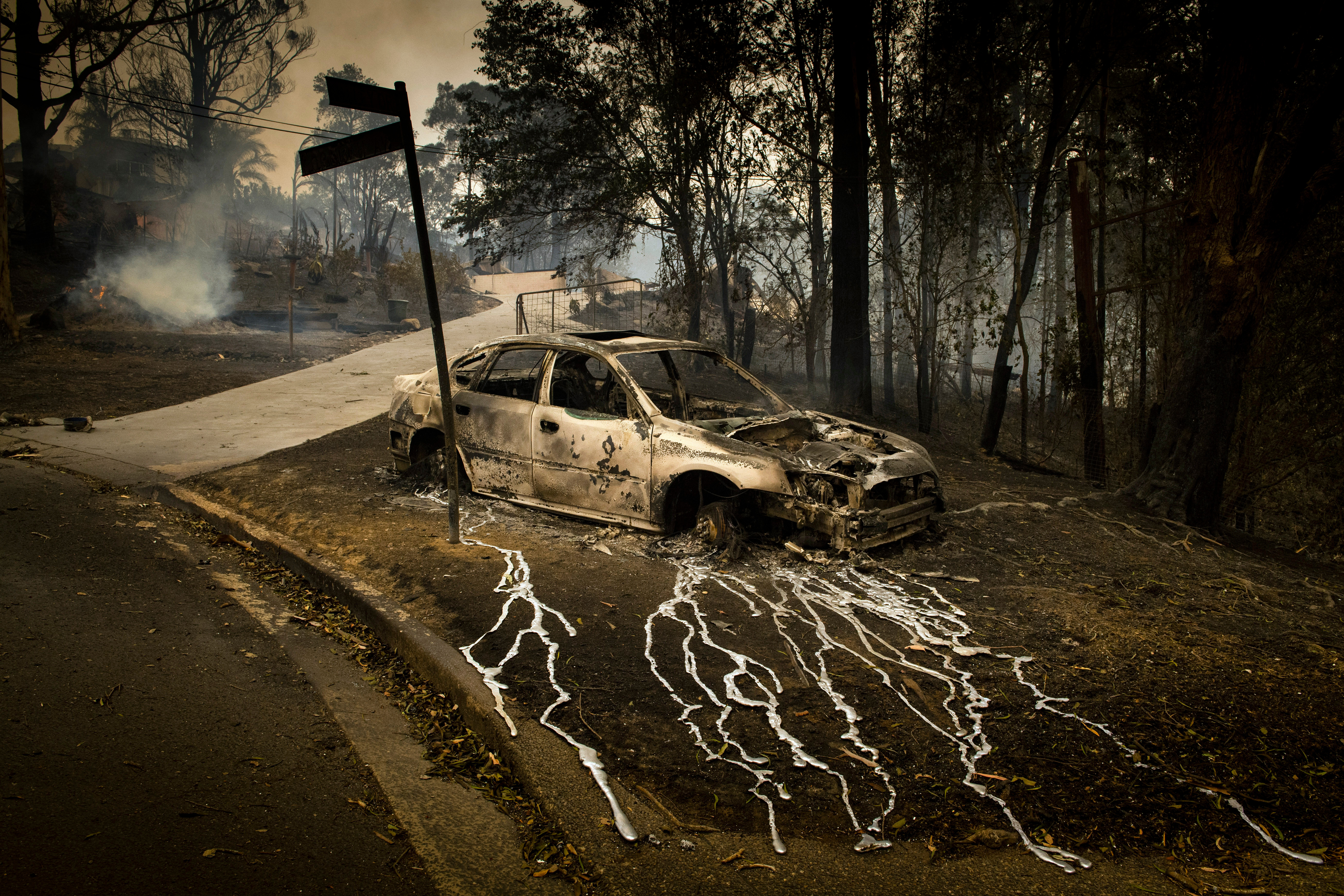 Molten metal streams off a burnt car after bush fires swept through Conjola, New South Wales