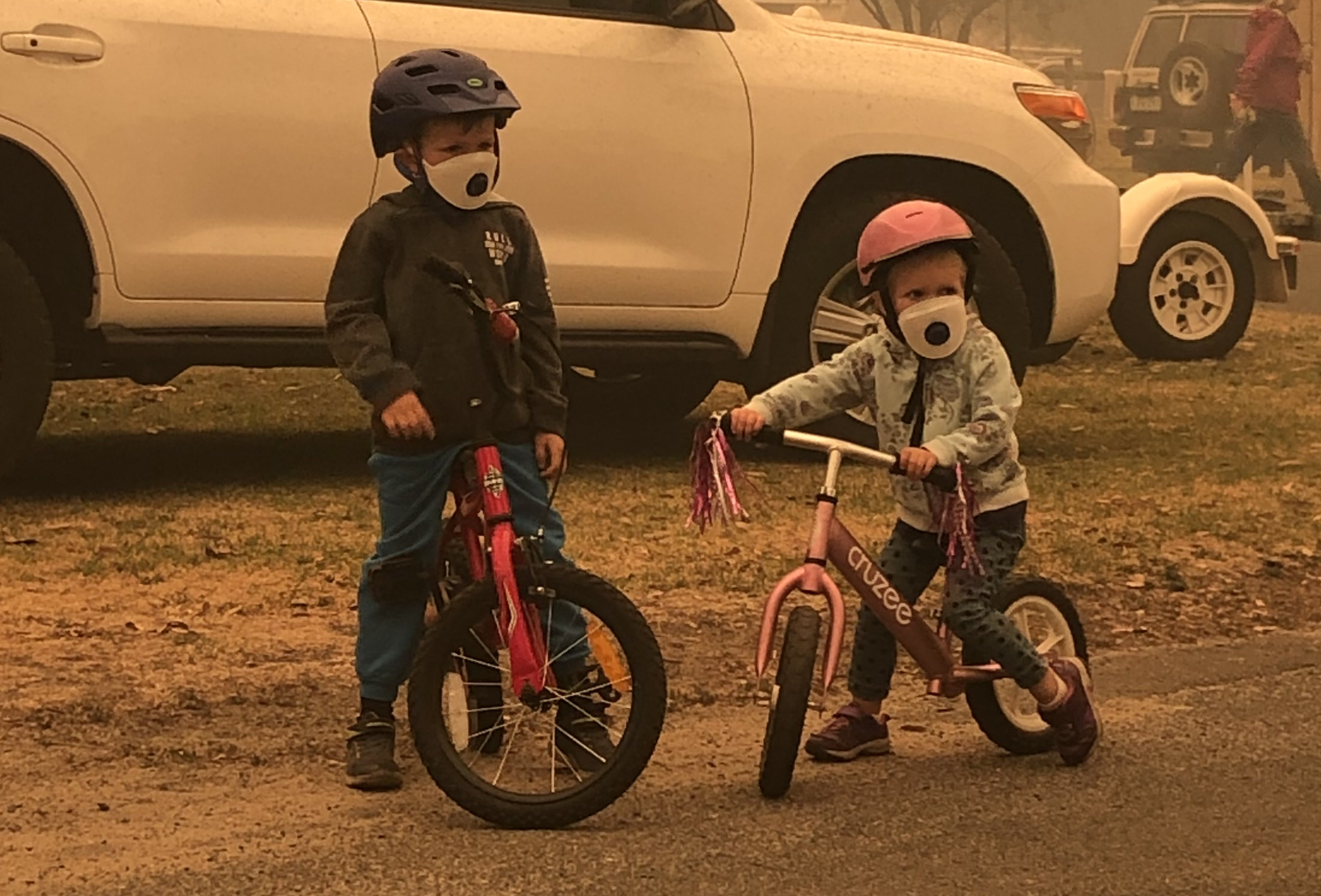 Two kids pictured on their bikes in Mallacoota, in Victoria