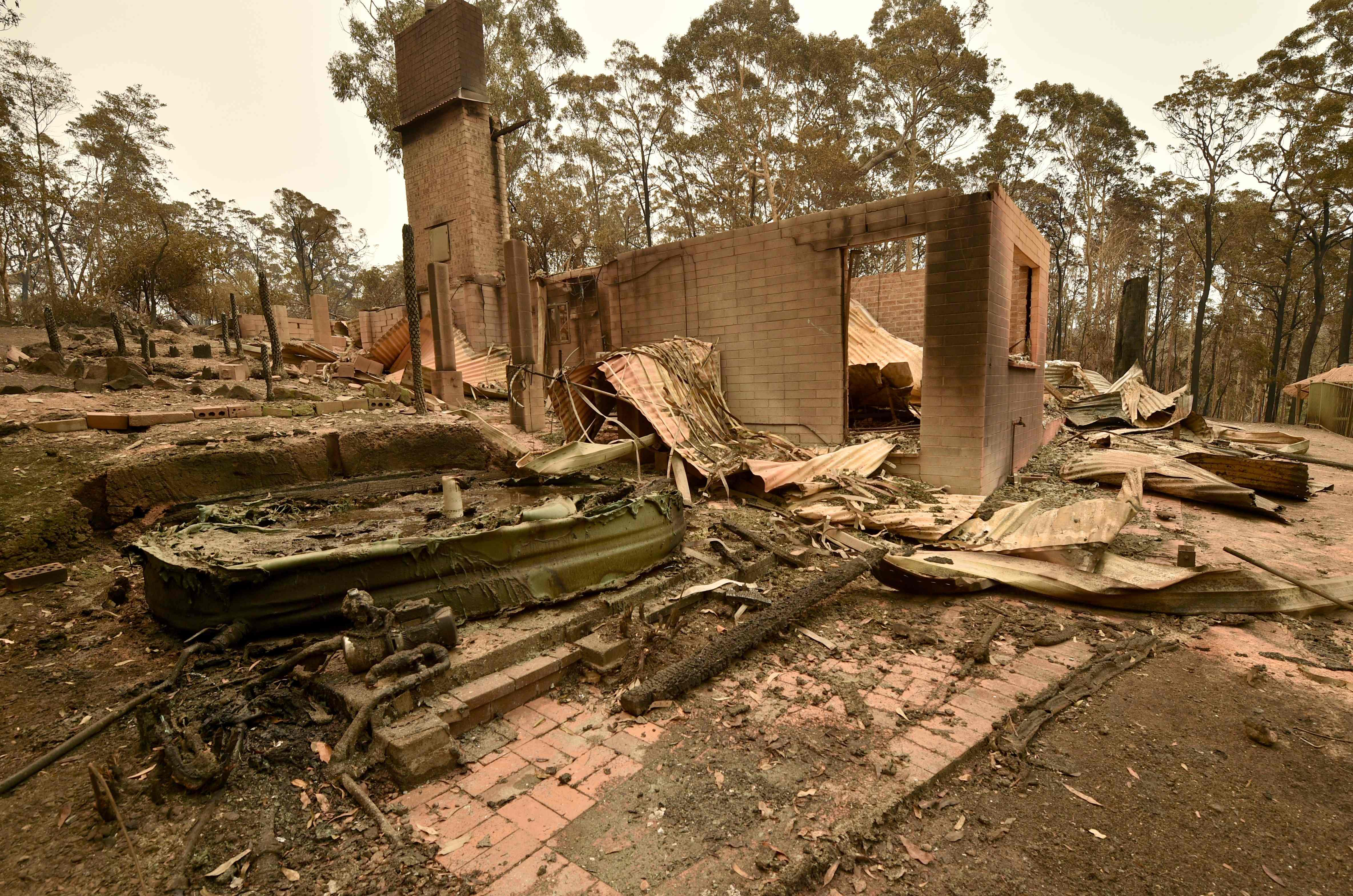 A home destroyed by fire in Bateman's Bay, where locals and tourists have been ordered to evacuate