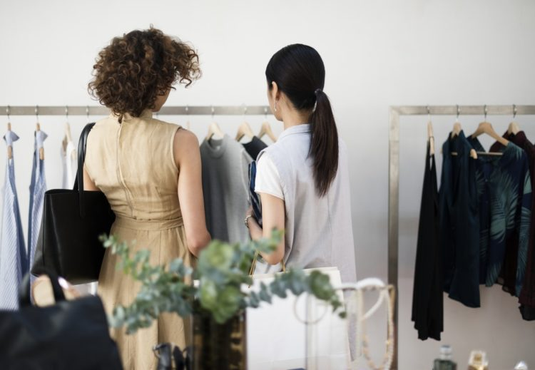 two women perusing a clothing rack in a store