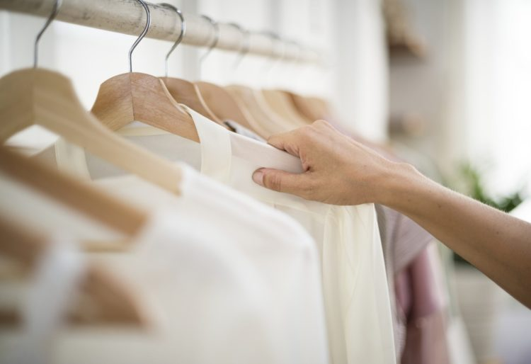 woman's hand selecting a blouse from a clothing rack