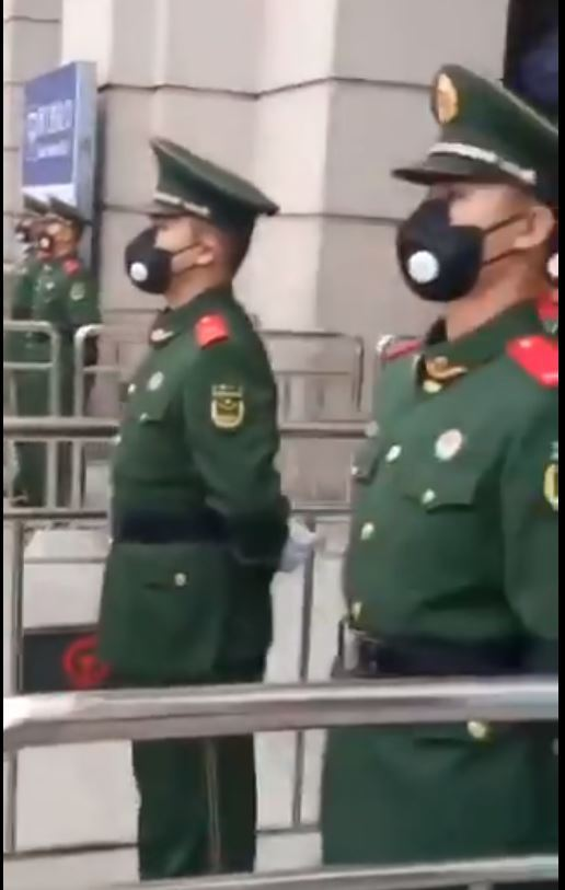 Authorities guard the train station in Wuhan while wearing masks