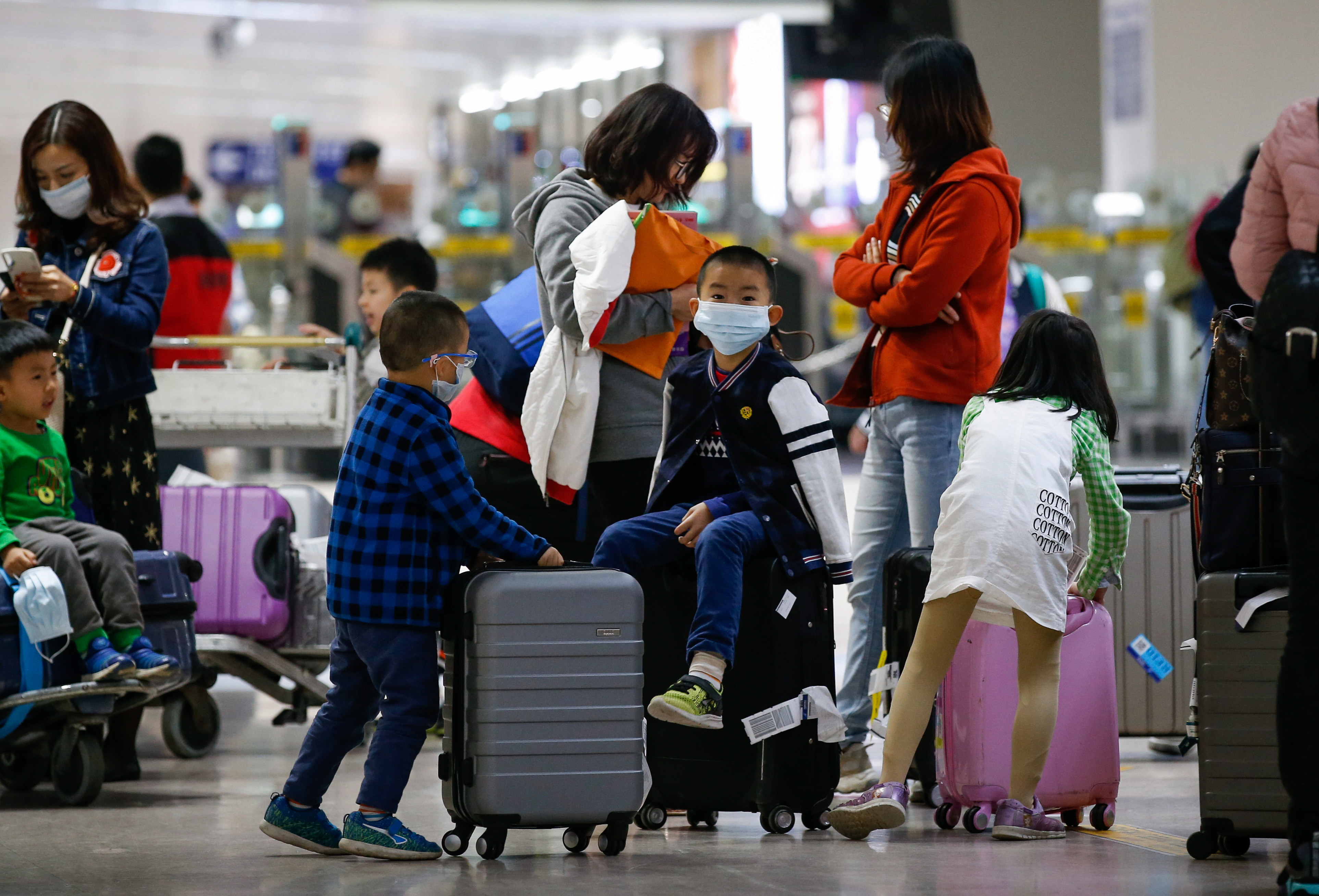 A boy wearing a face mask, who arrived from Guangzhou, China sits on top of a luggage at the Ninoy Aquino International Airport in Manila, Philippines