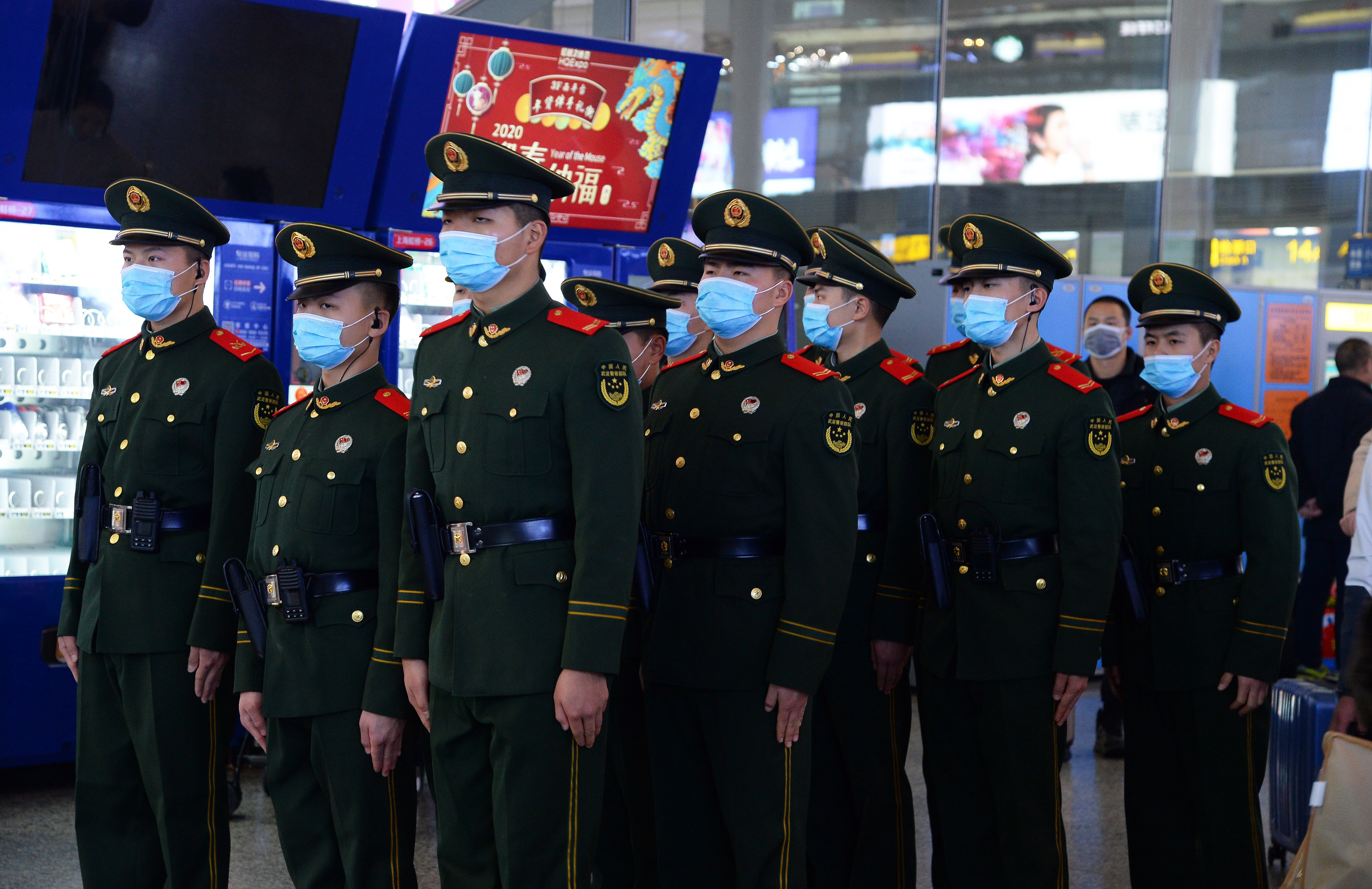 Chinese paramilitary police officers wearing masks patrol the Hongqiao Railway Station in Shanghai