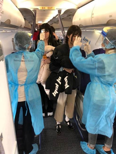 Officials measure temperatures of passengers on board on an Air China flight from Wuhan to Macau