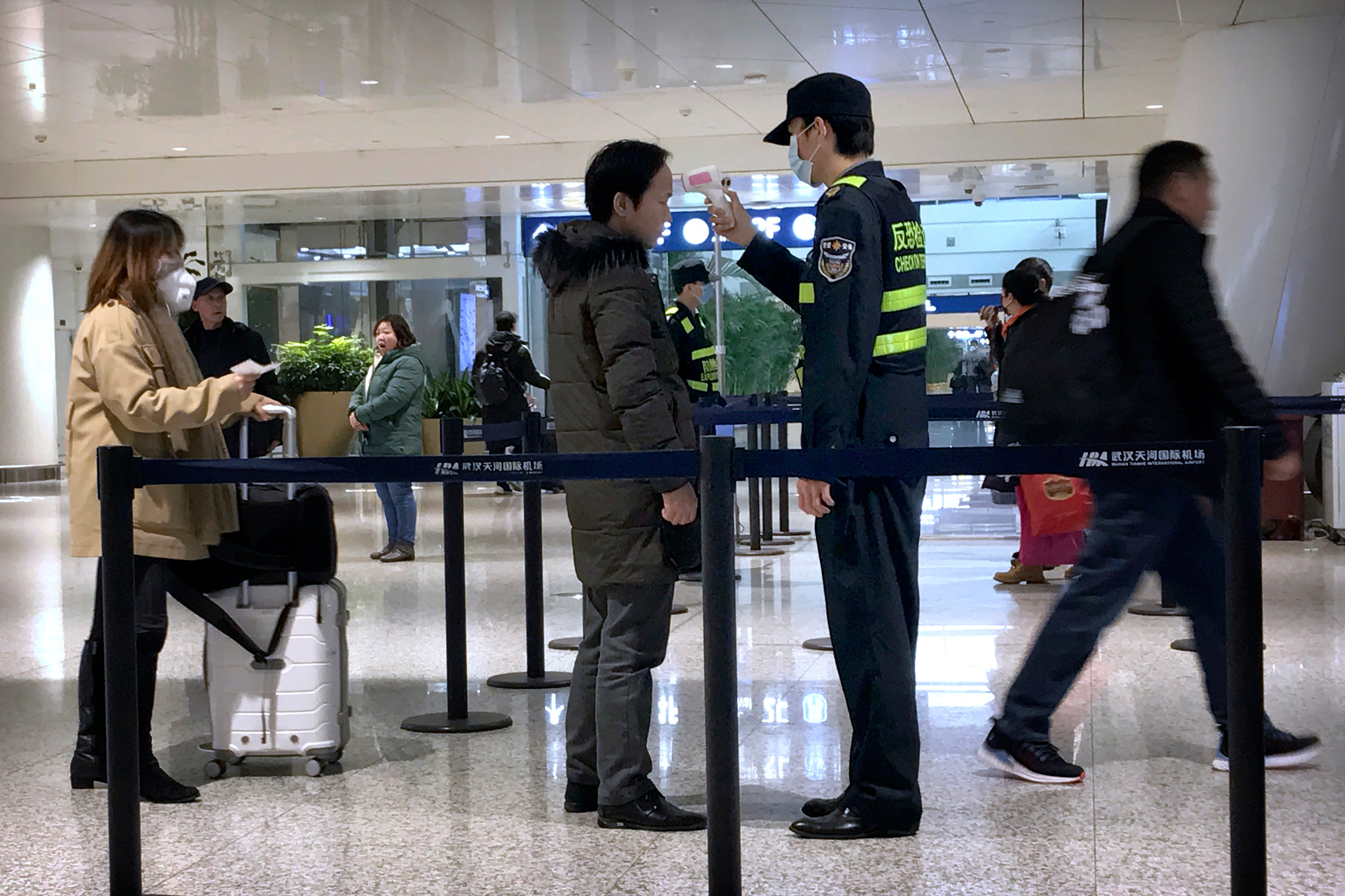 An official uses an infrared thermometer on a traveller at an airport in hard-hit Wuhan