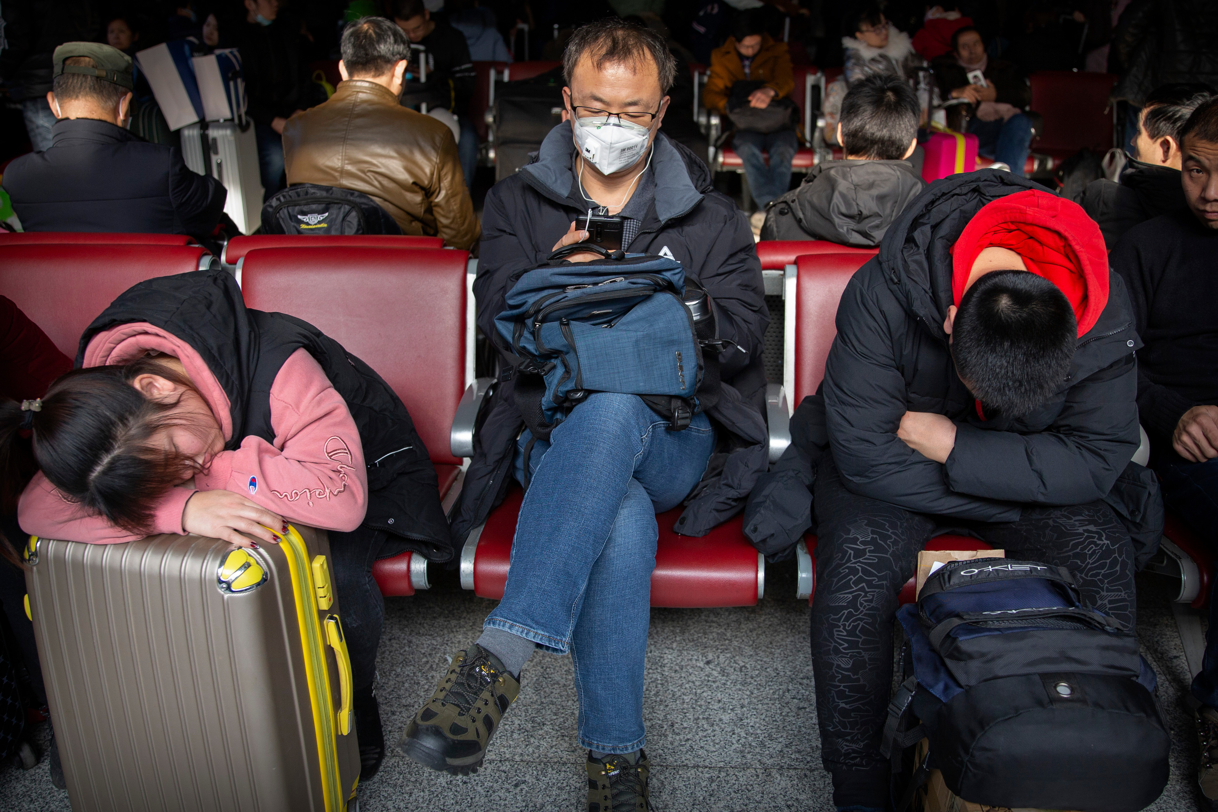 A traveller wears a face mask as he sits in a waiting room at the Beijing West Railway Station