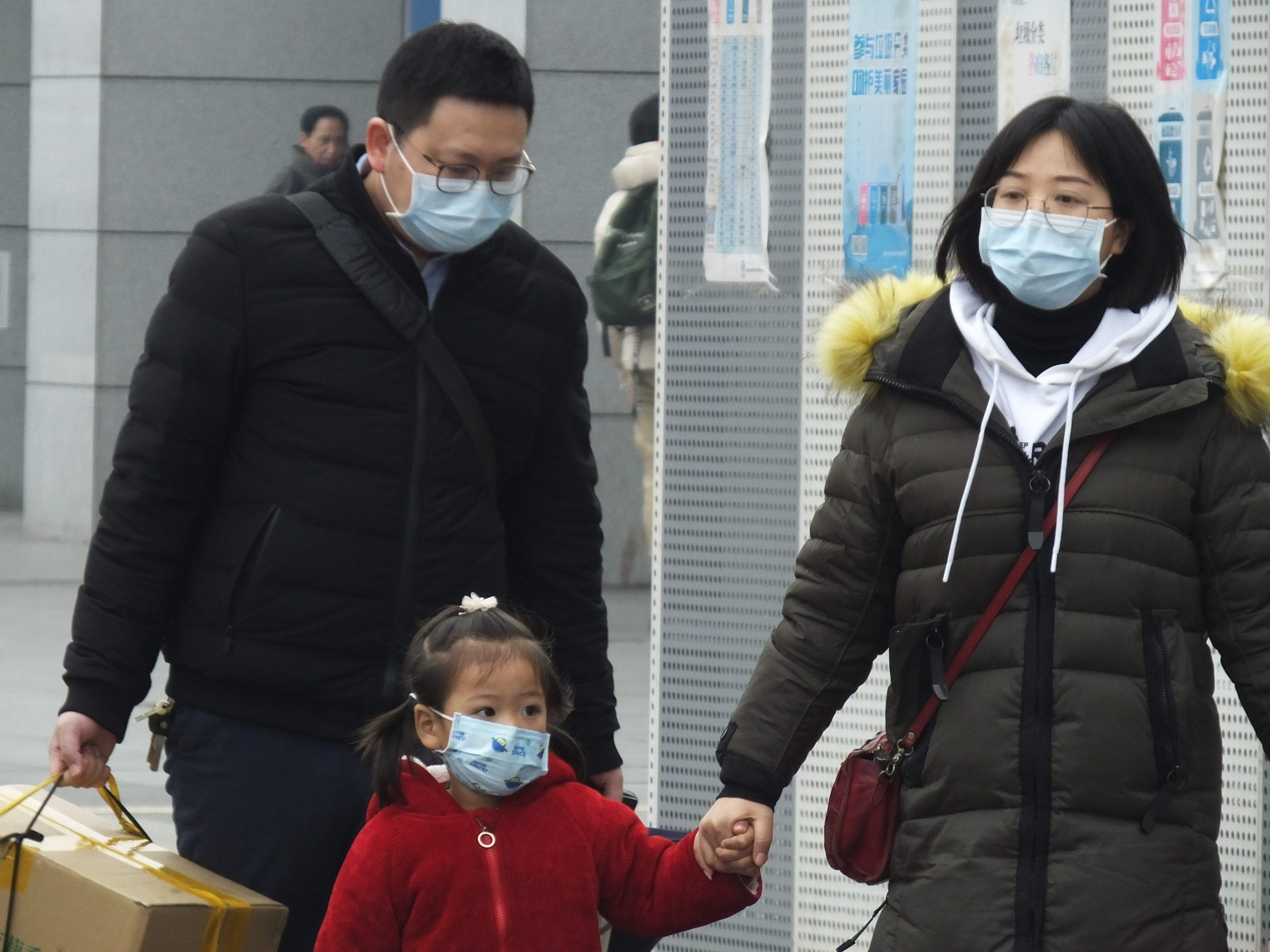Travellers wearing protective masks walk outside a railway station in Yichang in central China's Hubei province