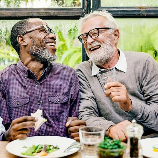 Senior men laughing and dining