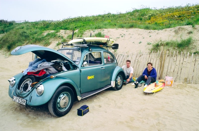 Surfer couple on beach with vw beetle