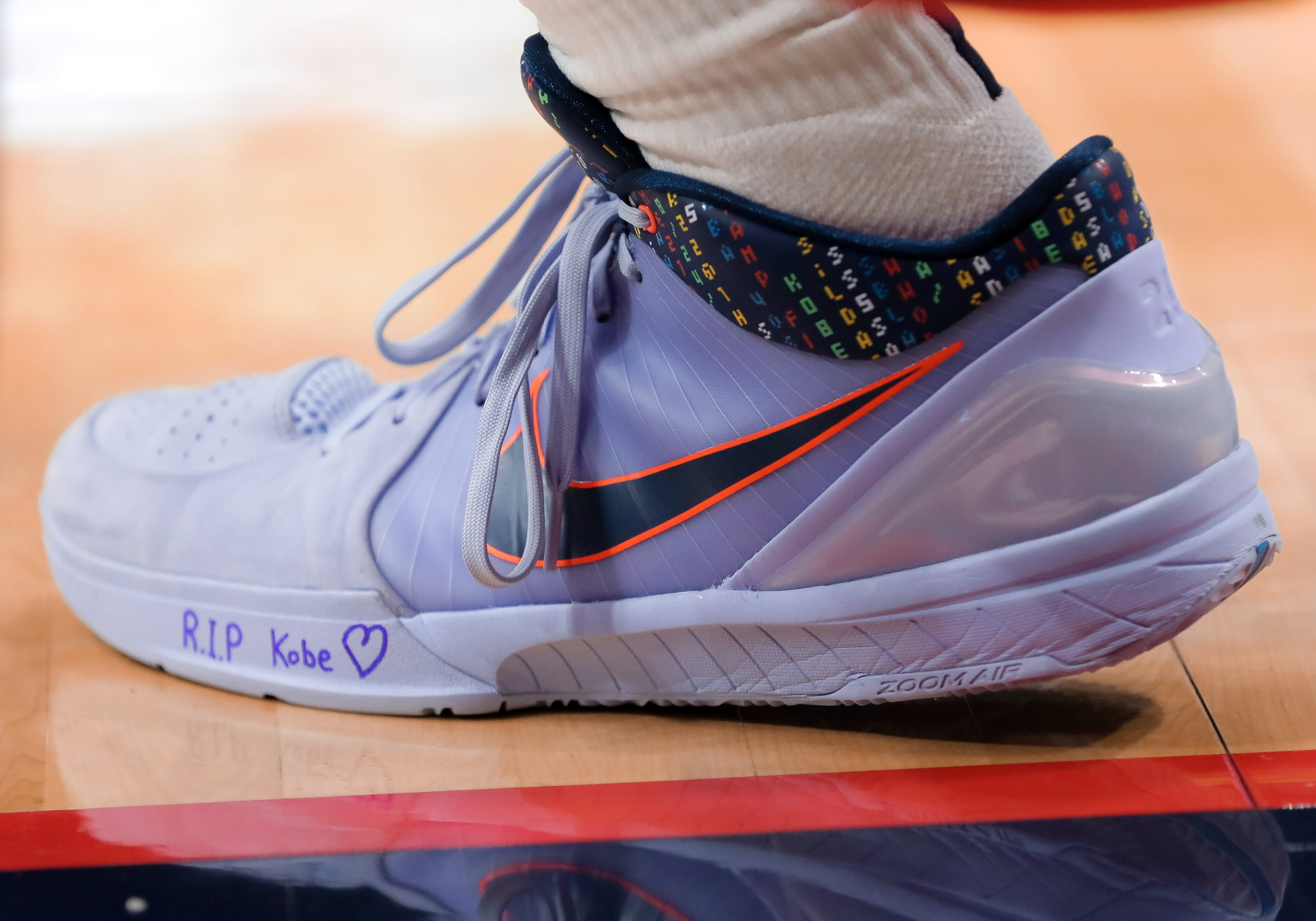 Players scribbled tribute messages to Bryant on their sneakers before stepping on the court Sunday