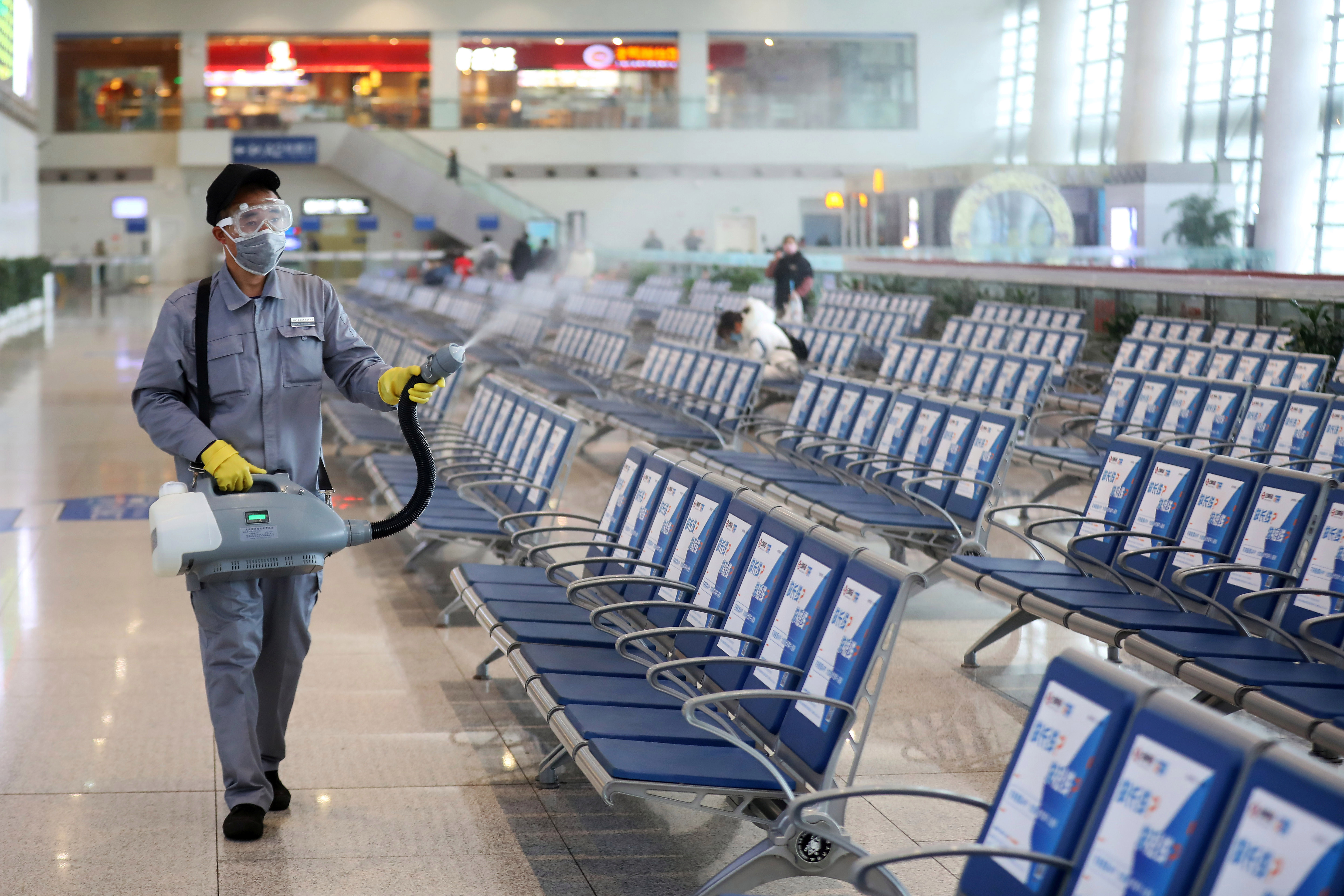 Workers in protective mask disinfects a waiting hall following the outbreak of a new coronavirus at the Nanjing Railway Station