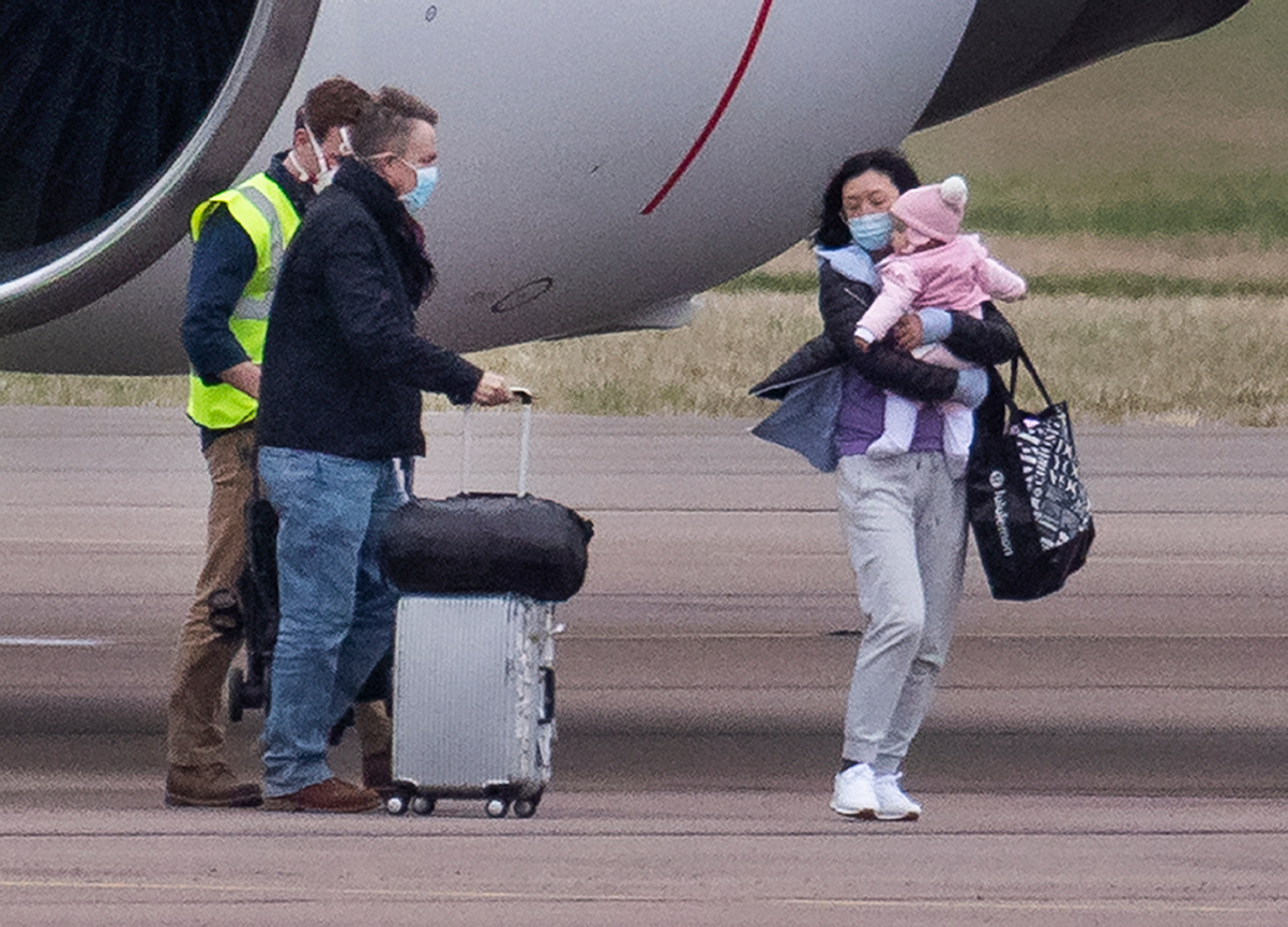 A mum carried a young girl after the Brits touched down in Oxfordshire