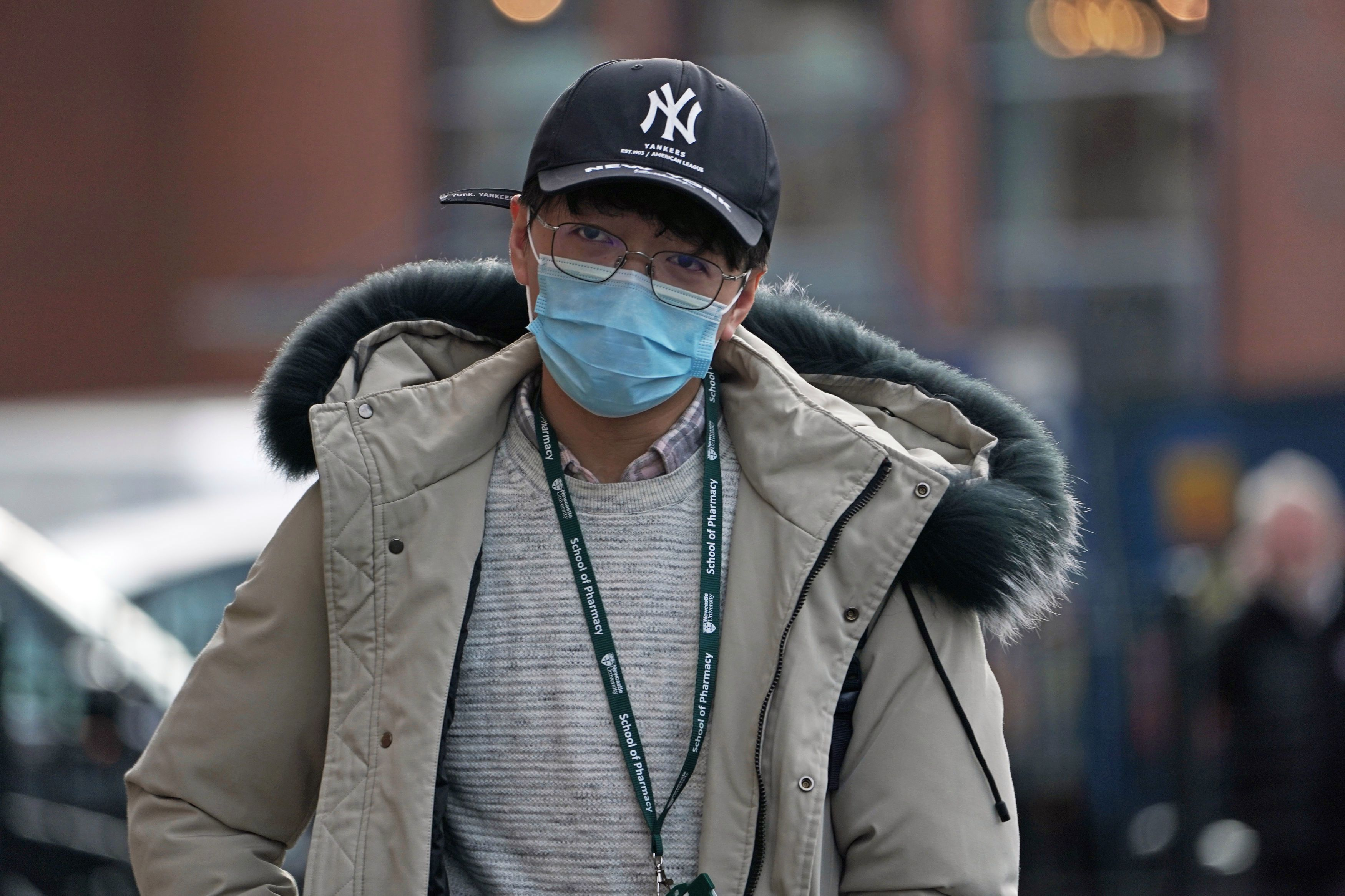 A man wears a mask in Newcastle upon Tyne, near where two patients who have tested positive for coronavirus