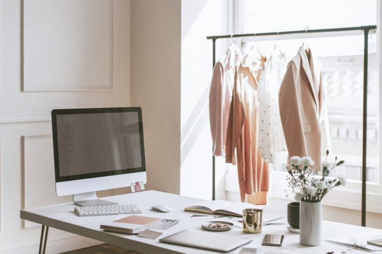 clothing on a rack behind a desk with a computer