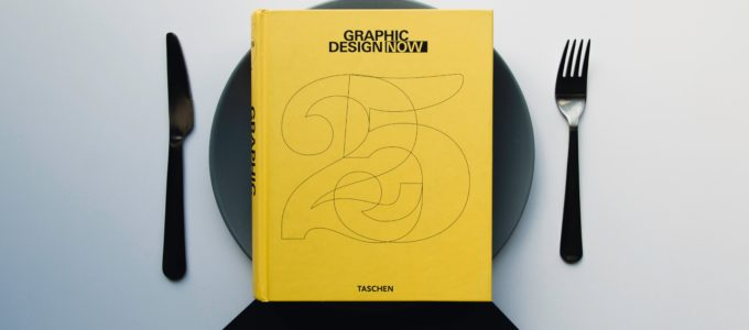 Graphic design book on a dinner plate with a knife and fork on either side